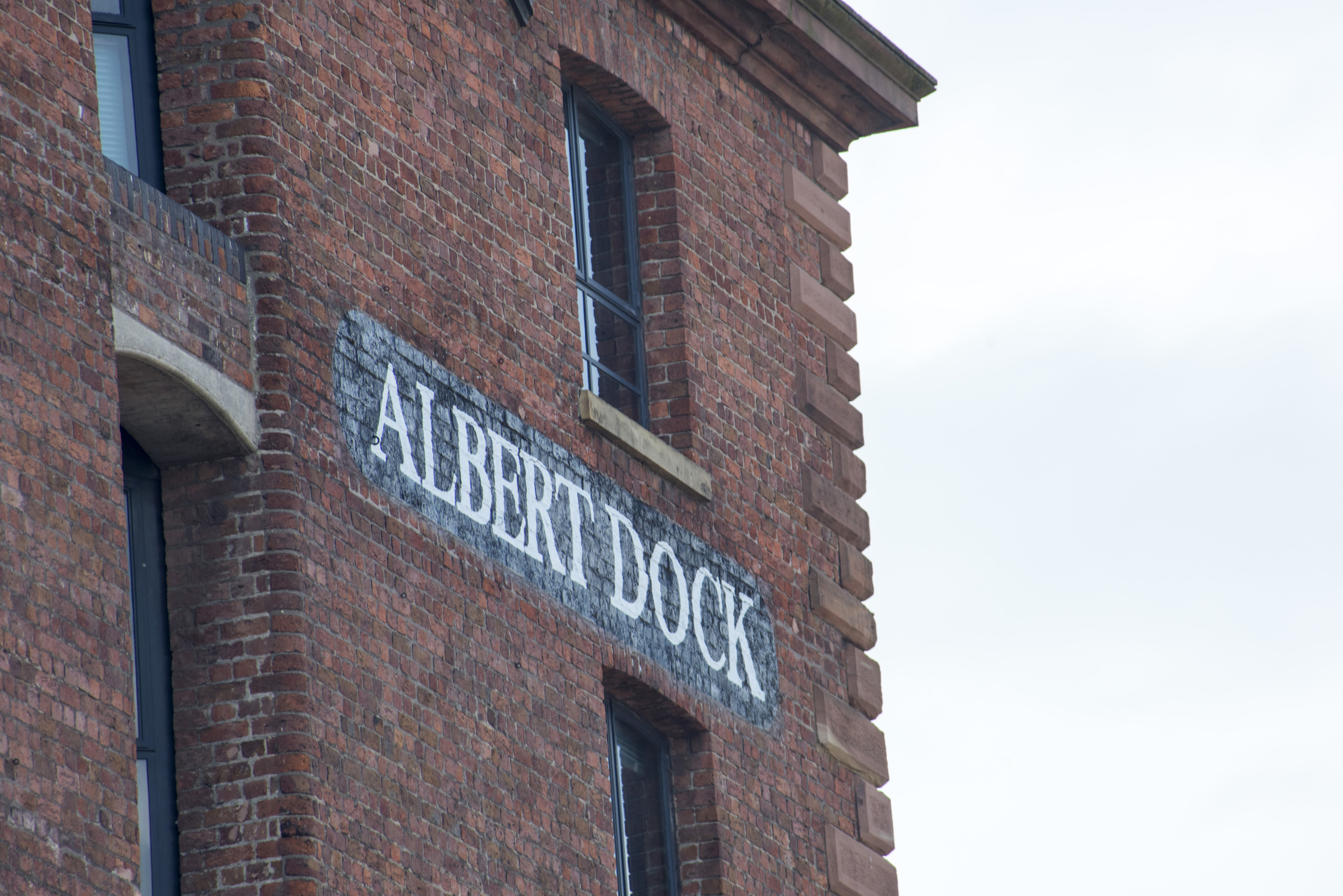 Detail on Albert Dock painted brick sign in between windows in Liverpool with over cast sky
