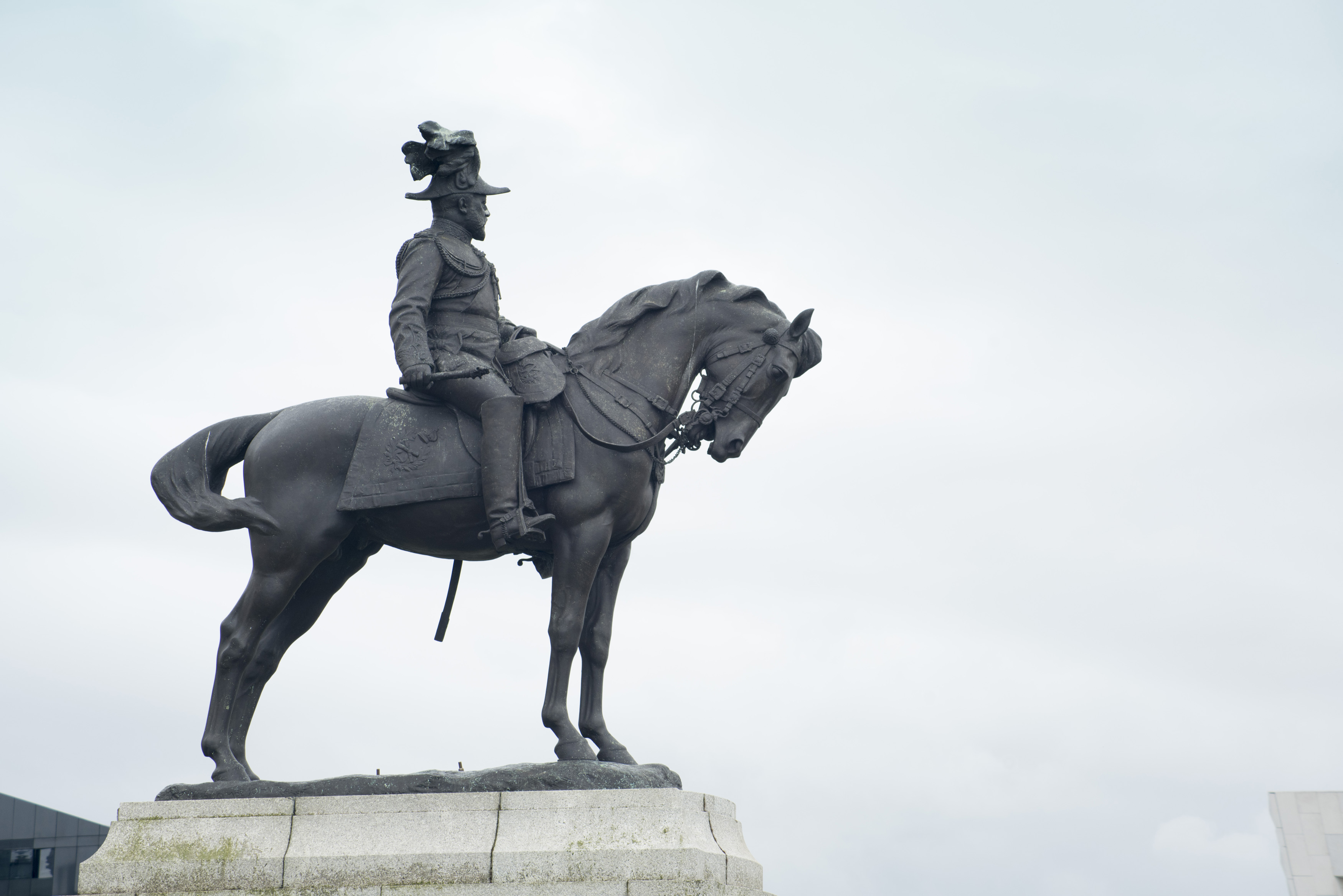 Side view of Edward the Seventh sitting on horse statue with copy space in overcast gray sky