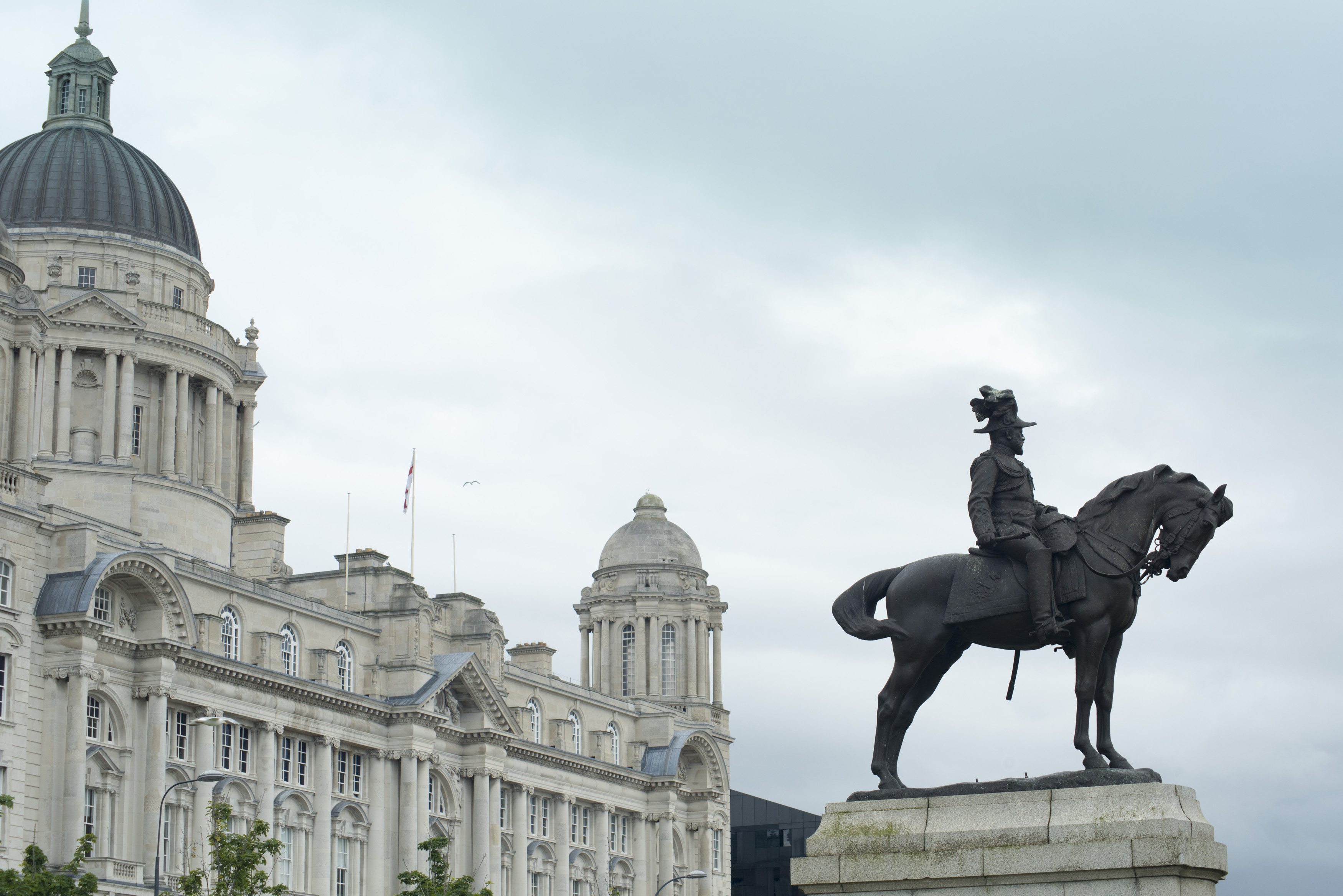 Statue of Edward VII on horse under overcast gray sky in Liverpool, United Kingdom. Includes copy space.