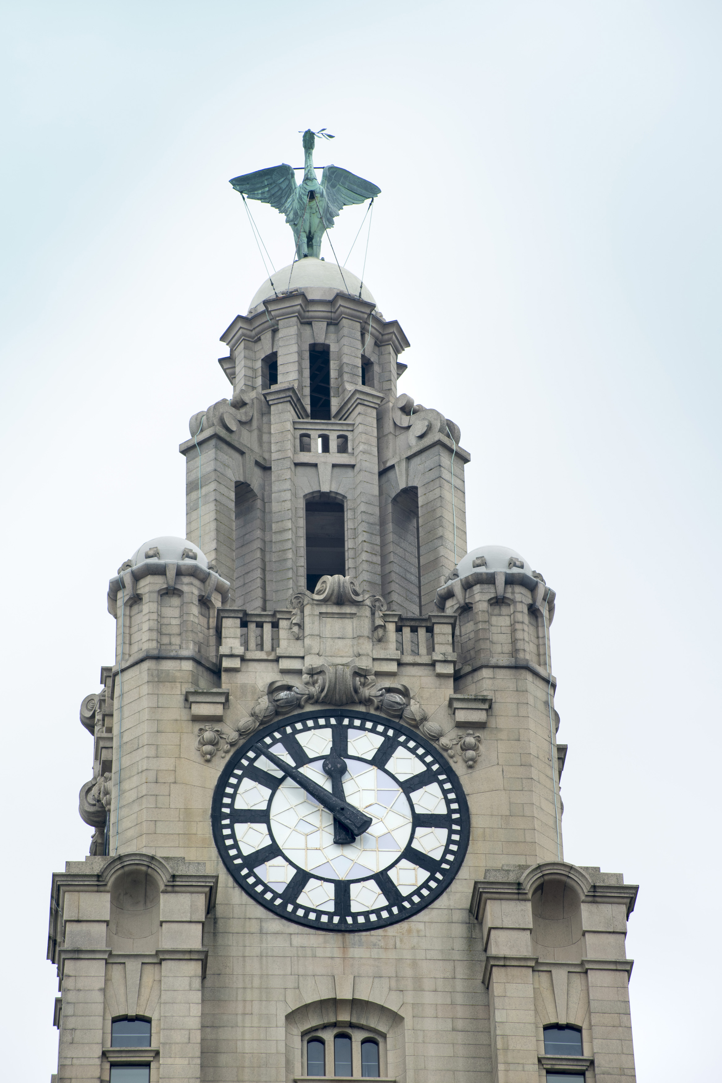 Close up on Liver Building clock tower with statue on top in Liverpool, United Kingdom