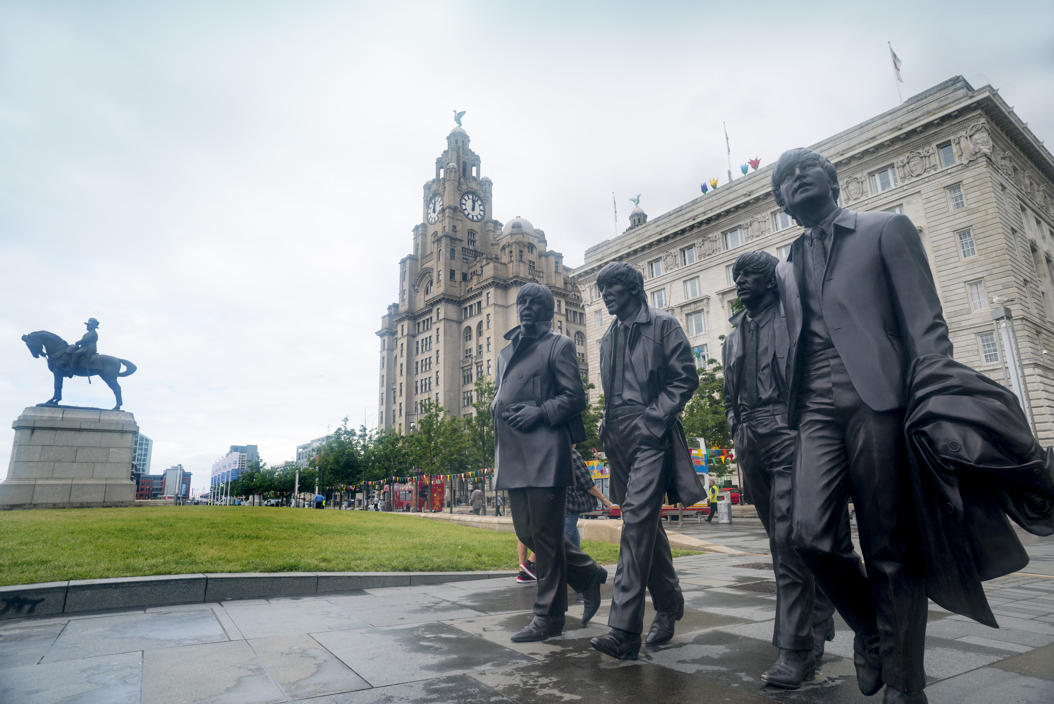Statues of the Beatles walking near the Liver Building in Liverpool, United Kingdom