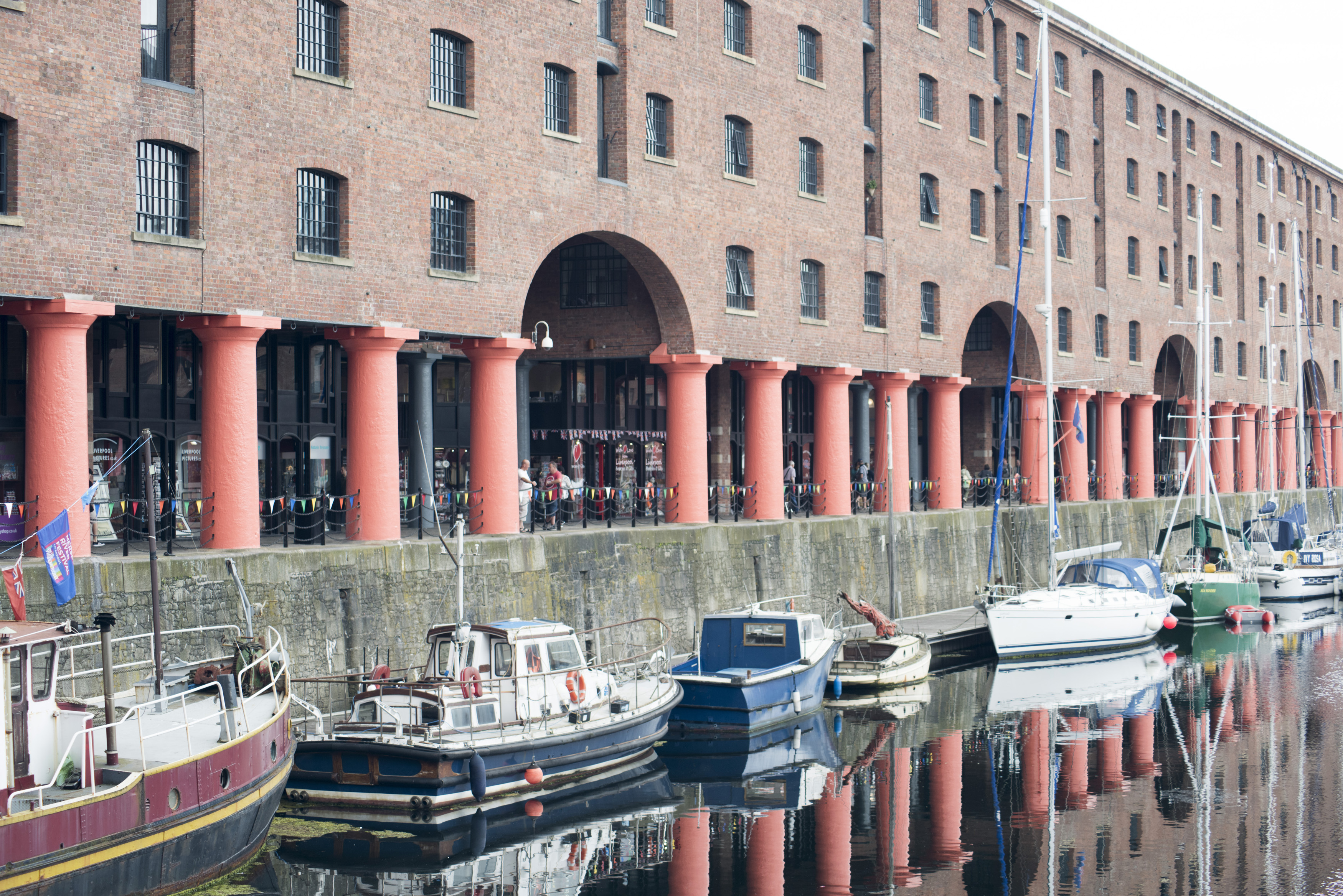 Large red support columns reflecting in water with various little boats docked at Liverpool Albert