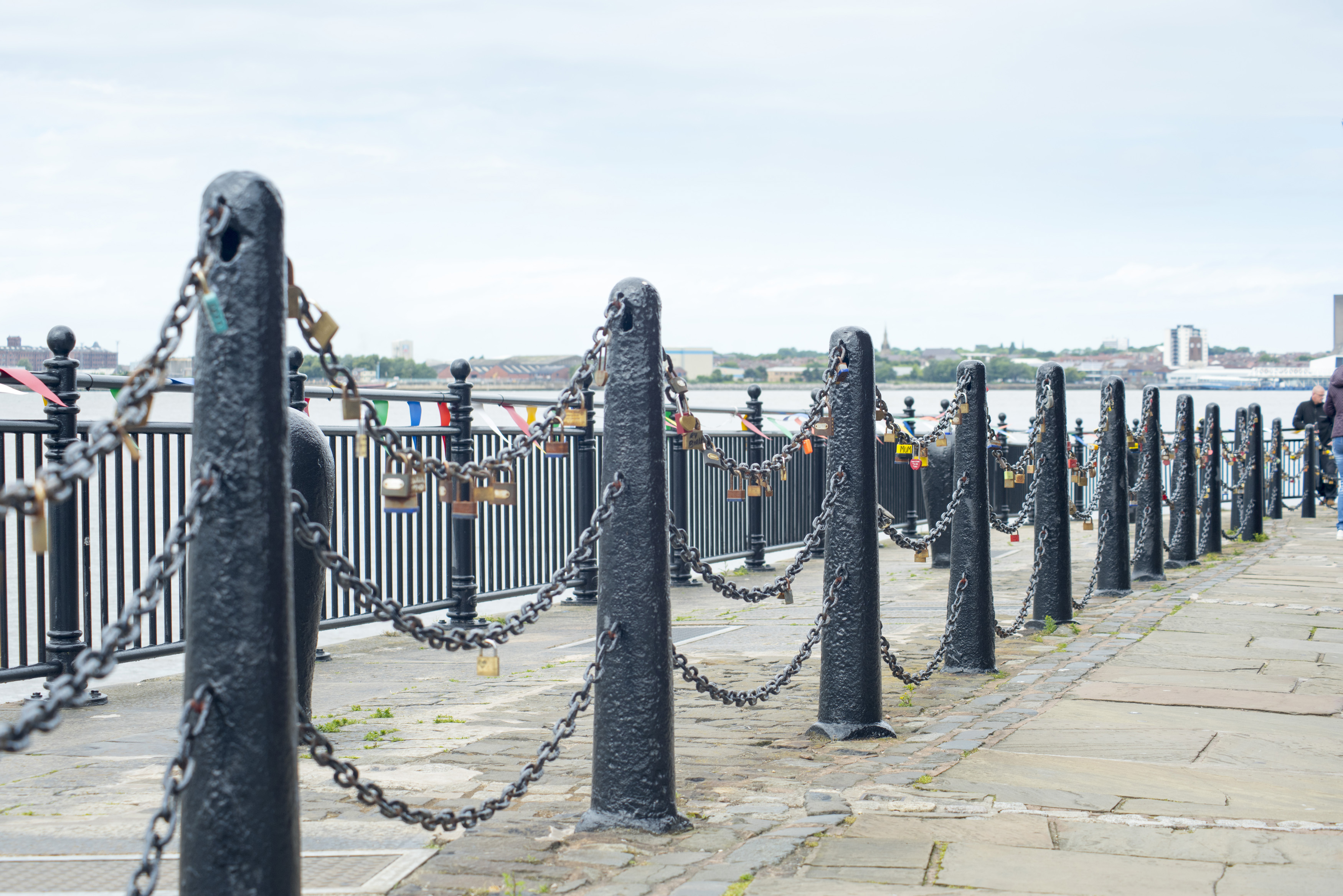 Various padlocks on iron chains at waterfront at Liverpool Mersey waterfront in the United Kingdom