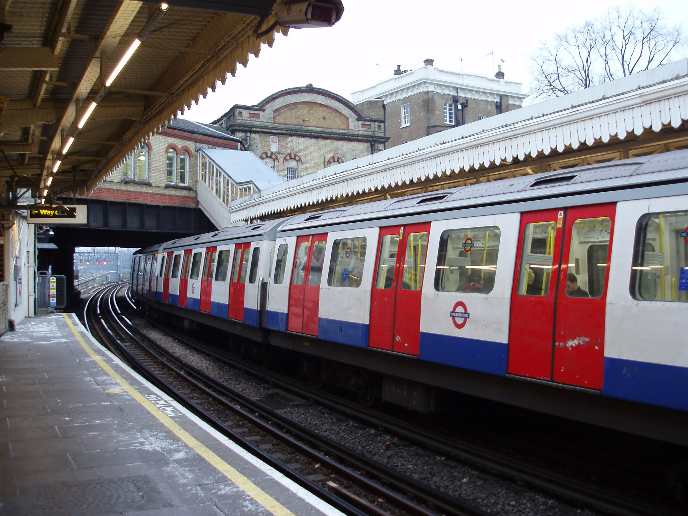 Overground underground subway train or tube train parked at an above ground platform at a station in London waiting for passengers to embark