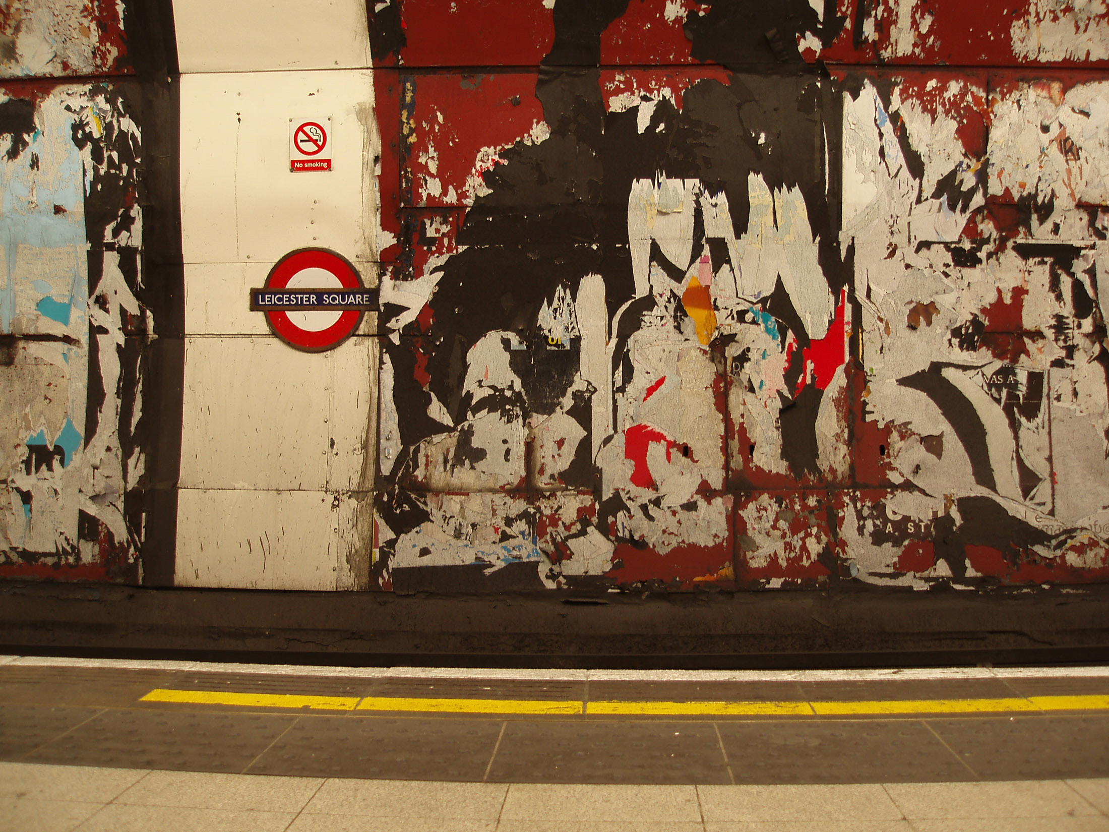 Grungy walls on the platform at the tune station London underground with remnants of posters and advertising and flaking paint