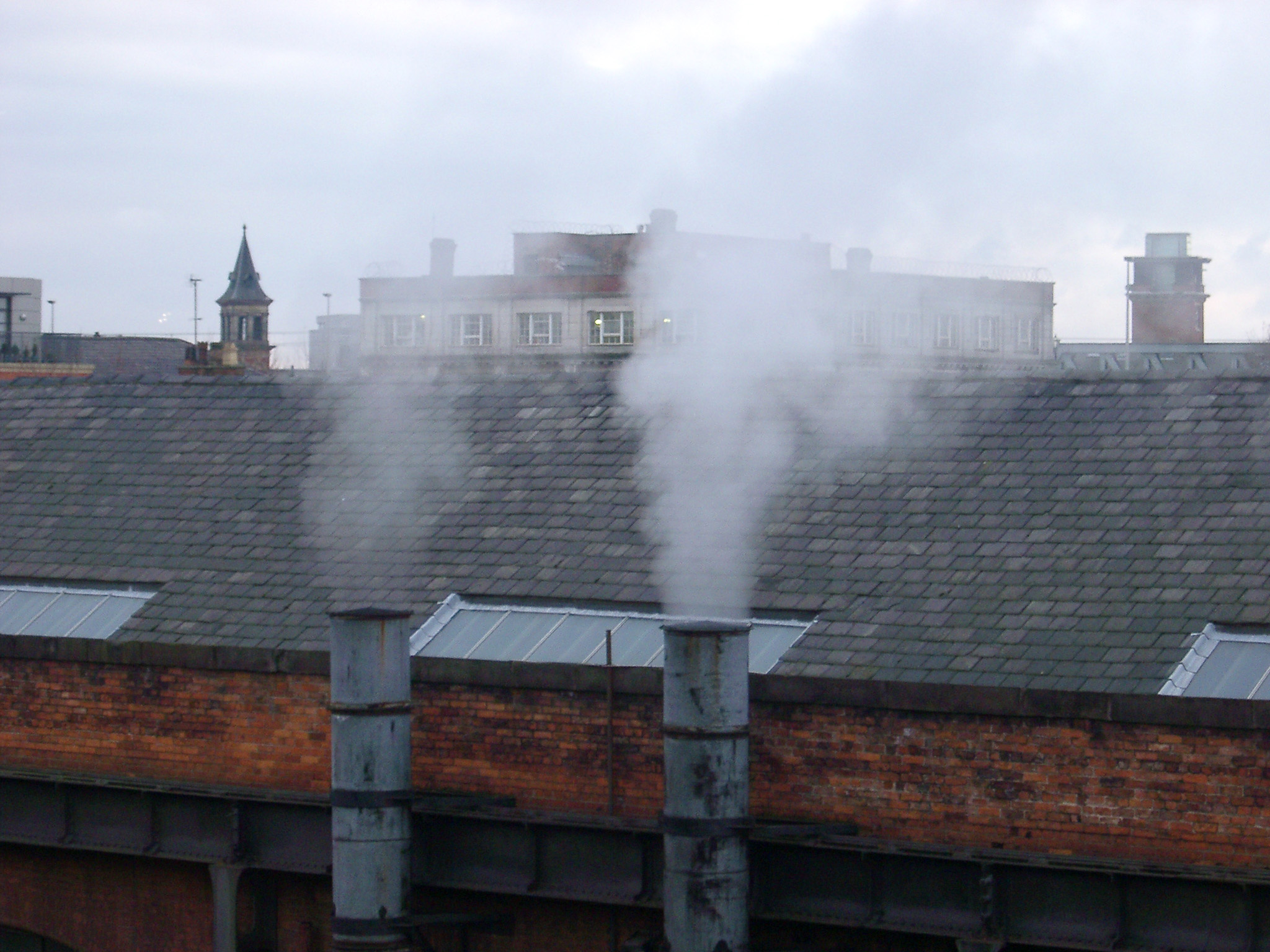 Two factory smoke stacks spewing steam into the air in industrial Manchester at the MOSI museum, Lancashire, England