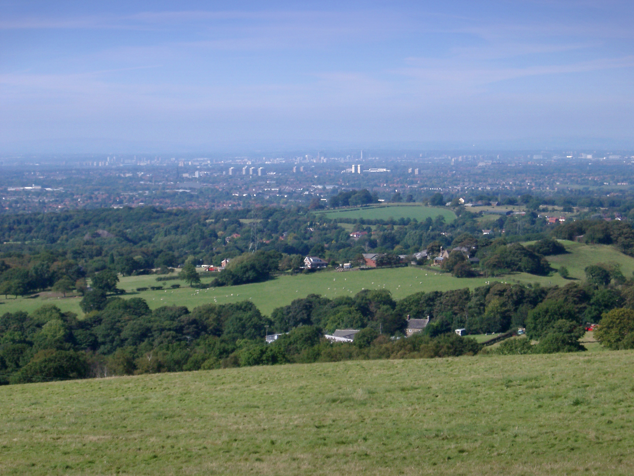 Lush English countryside looking towards the city of Manchester in the distance with the view encompassing the whole city