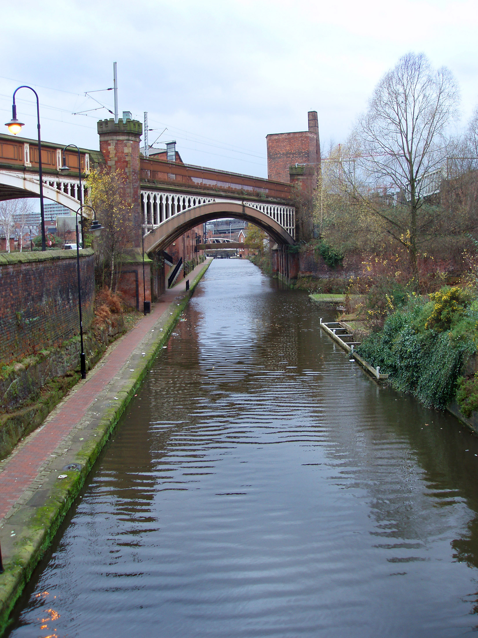 Manchester canal towpath leading under the old arched red brick railroad to the industrial warehouses now part of the Castlefield conservation area