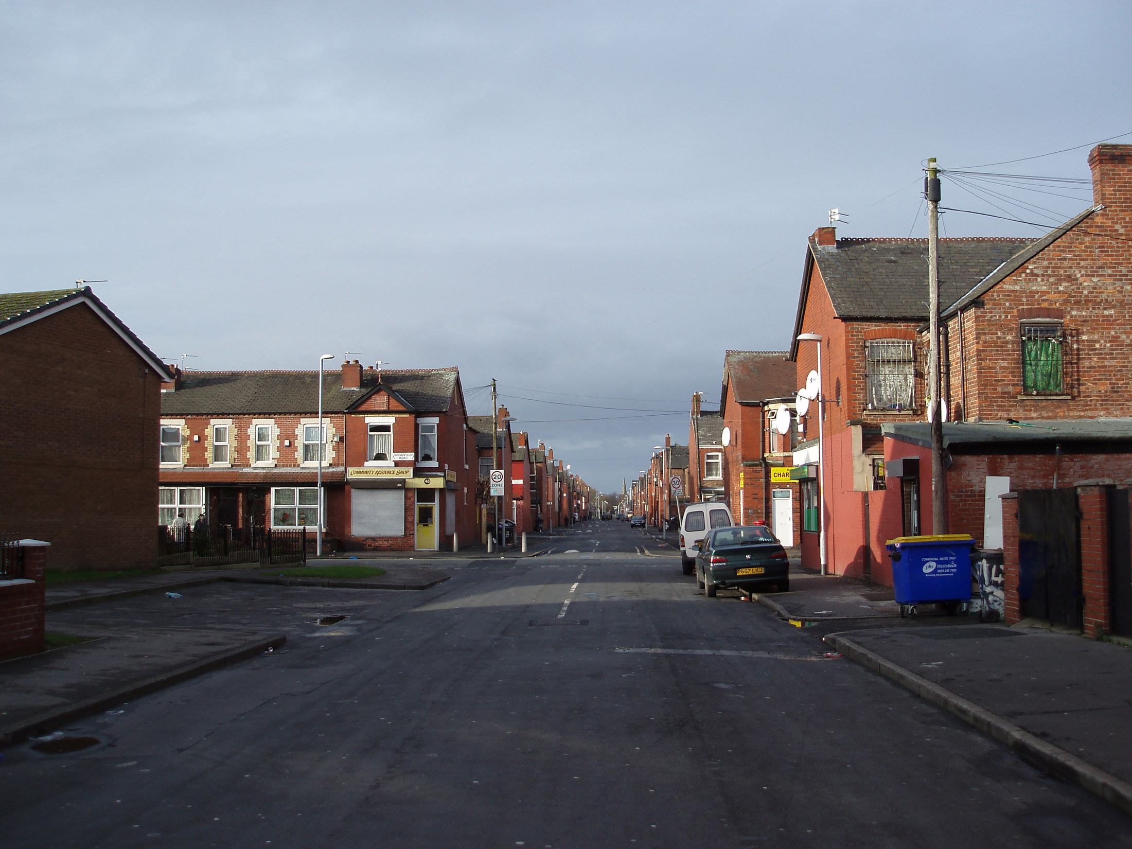 Side street in Moss, Manchester showing the typical red brick architecture, parked cars and a garbage bin