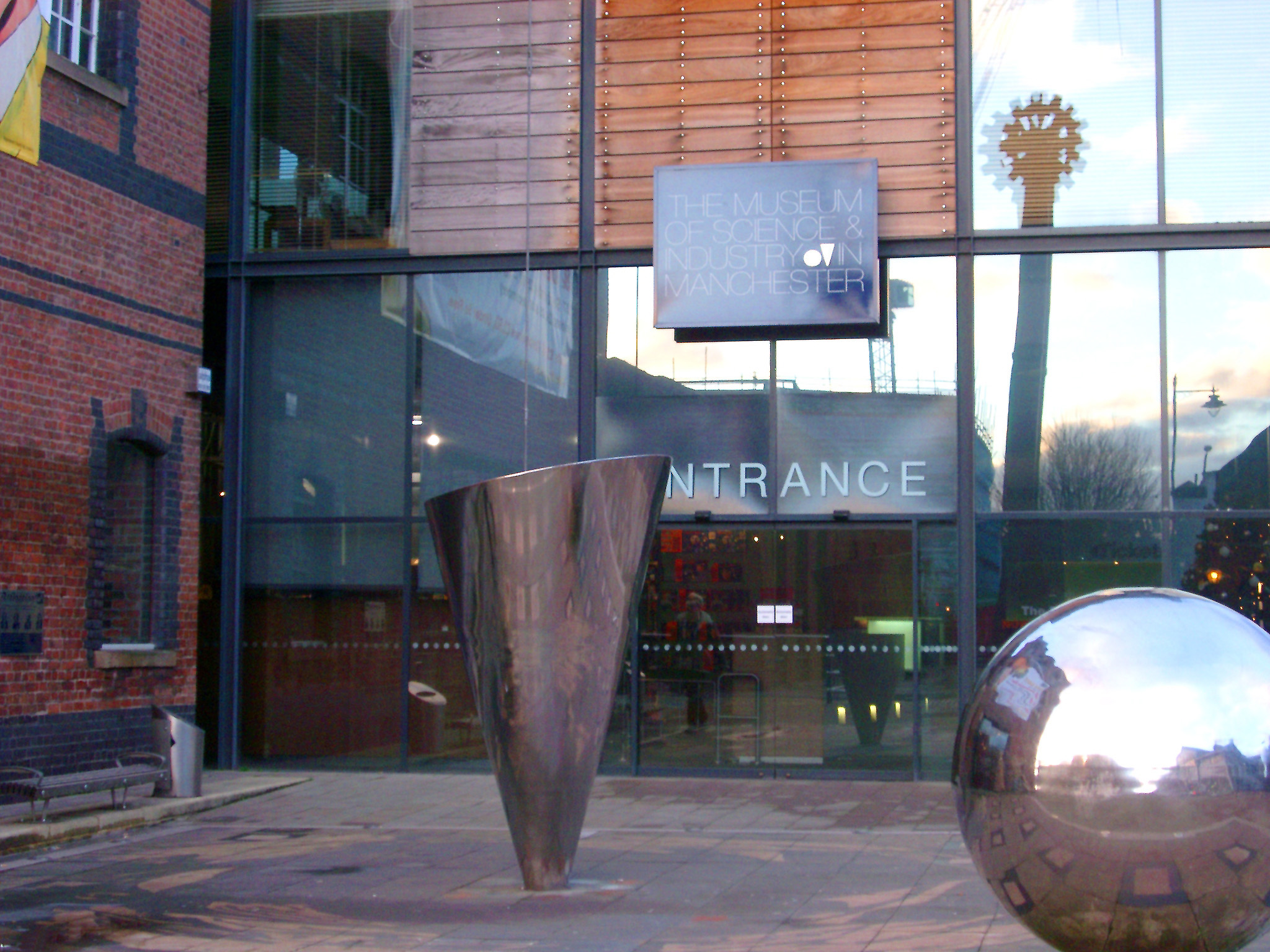 Entrance to the Manchester Museum for science and industry with on outdoor sculpture of a shiny metal silver sphere