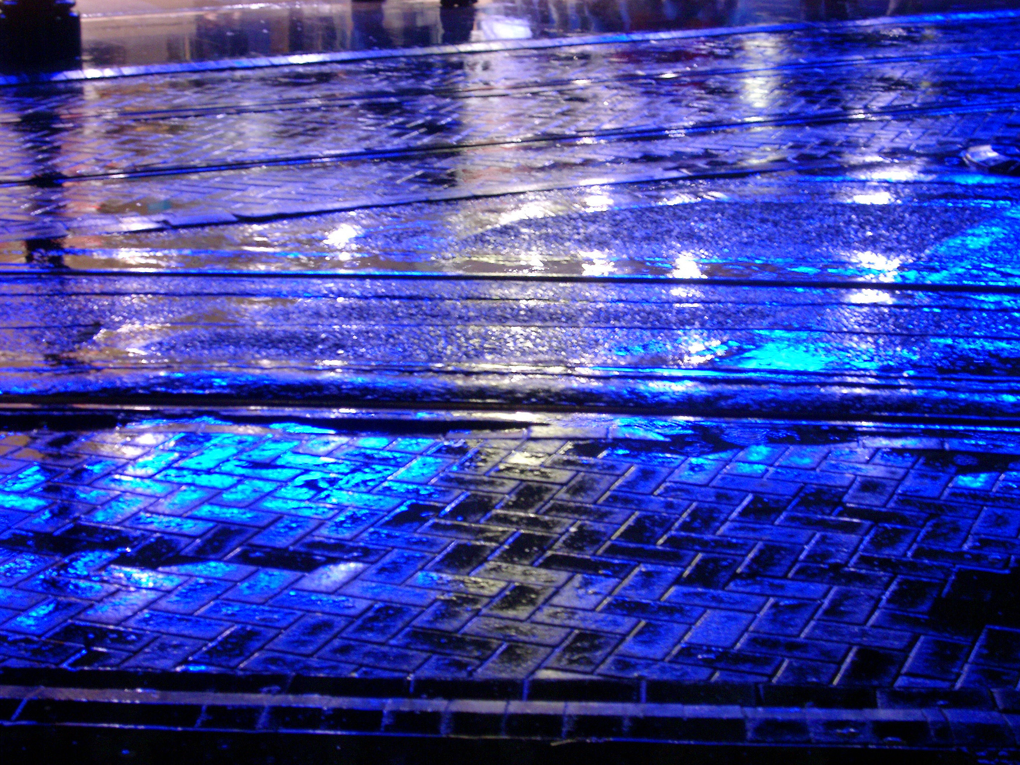 Rain falling on an urban sidewalk at night with blue reflections from lights in the layer of moisture for a colorful background