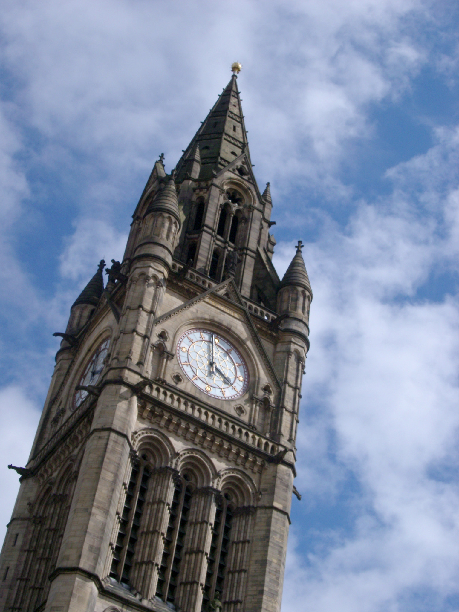 Ornate Gothic revival external facade of the Manchester Town Hall clock tower against a cloudy blue sky