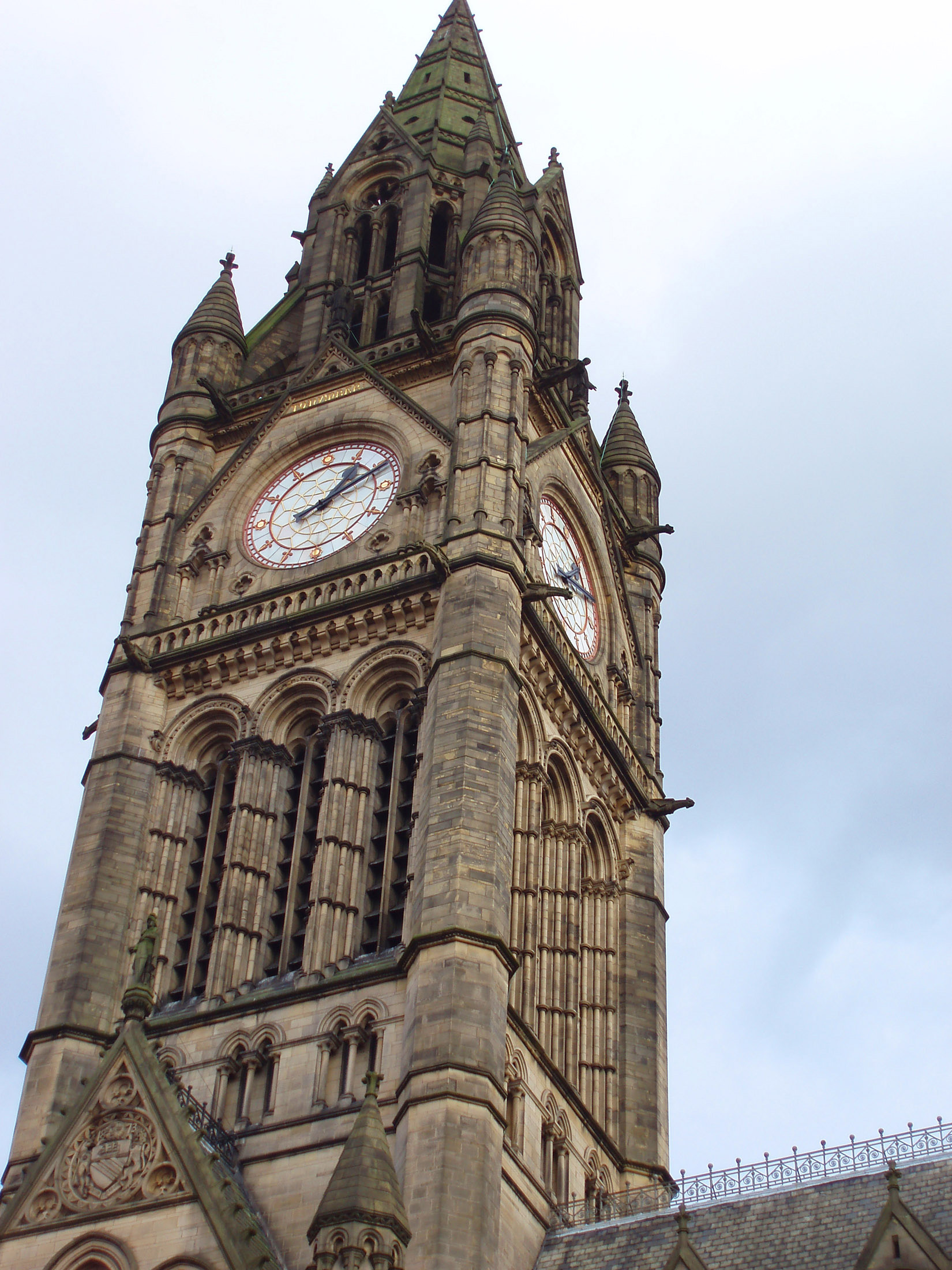 Exterior ornate stone facade of the Gothic revival clock tower on Manchester Town Hall with its four clock faces, Lancashire, UK
