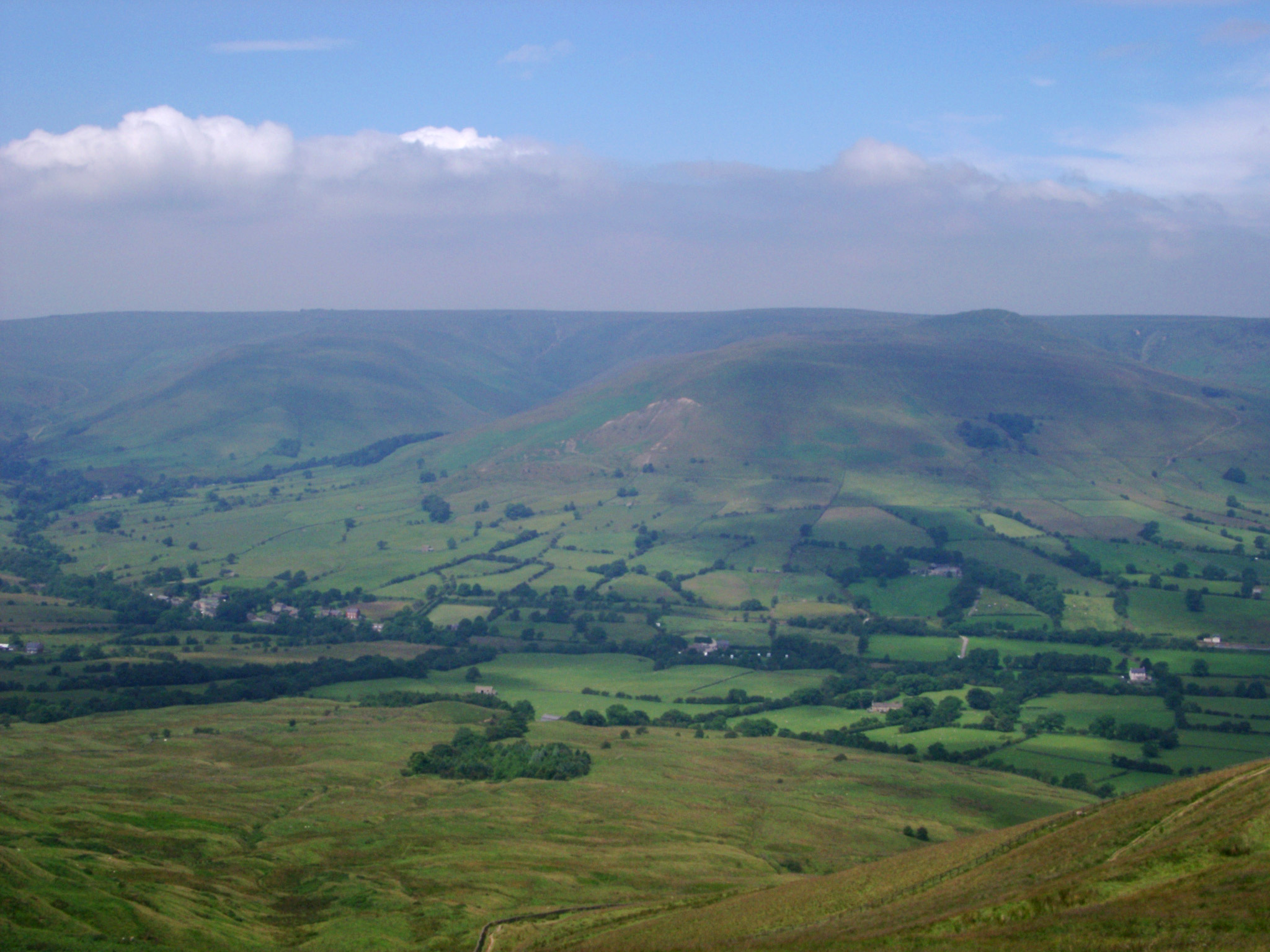 View from Mam Torr to Kinder Scout at Edale with a lush green scenic panorama across rolling hills to the plateau, Derbyshire, UK