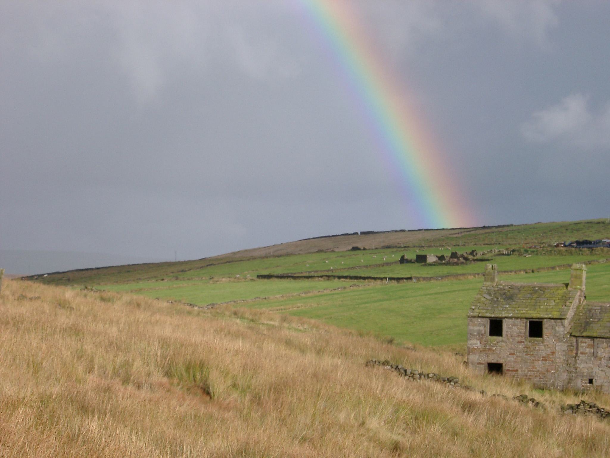Ruined abandoned building in the Pennines on a stormy day with grey skies and a colorful rainbow