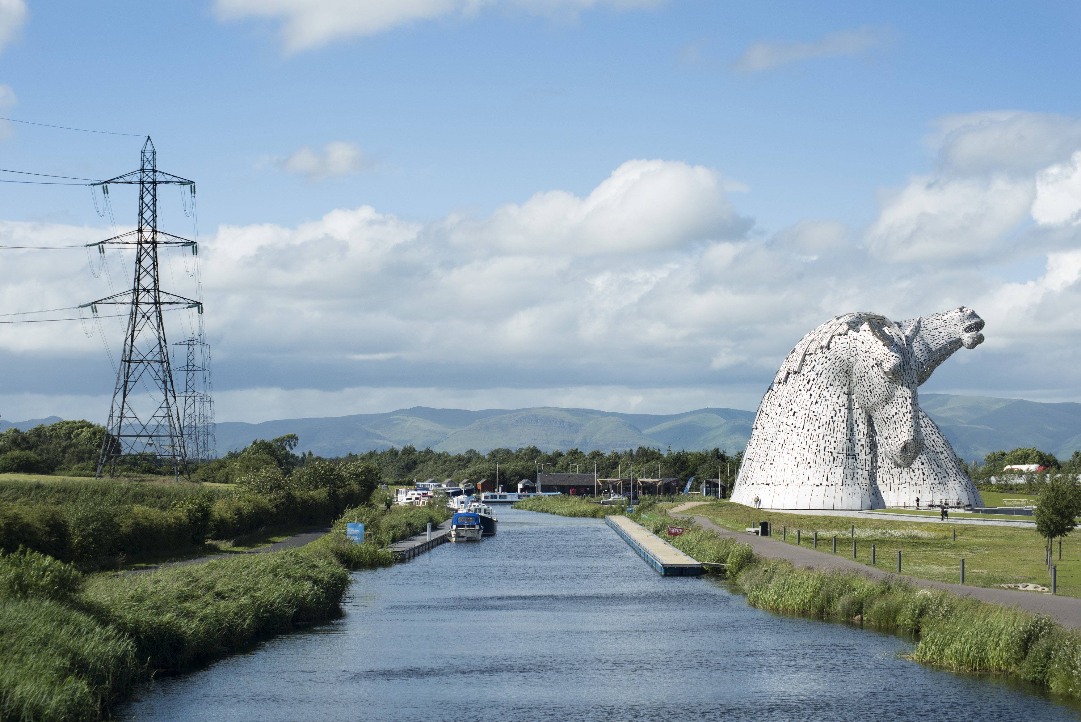 Scenic view of Falkirk Scotland with kelpies sculpture of horse heads on right side of the canal