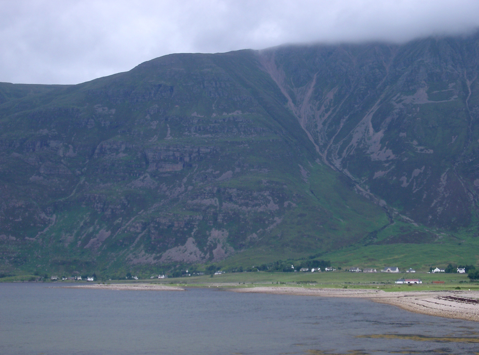 Beach and small settlement on the shores of a loch in the Scottish highlands pictured on a cold misty day