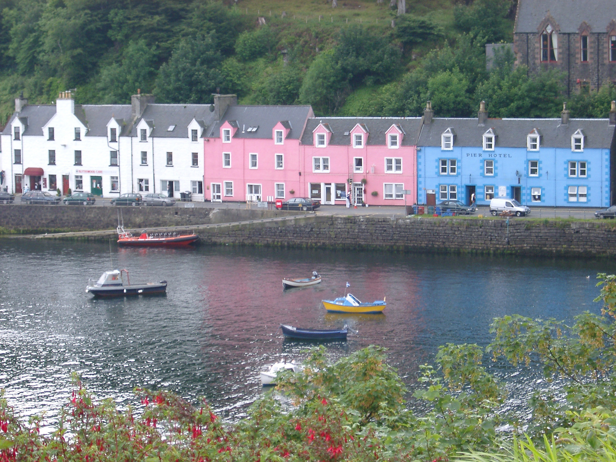 Colorful terraced houses and hotel on the waterfront overlooking fishing boats on the water in Portree, Isle of Skye