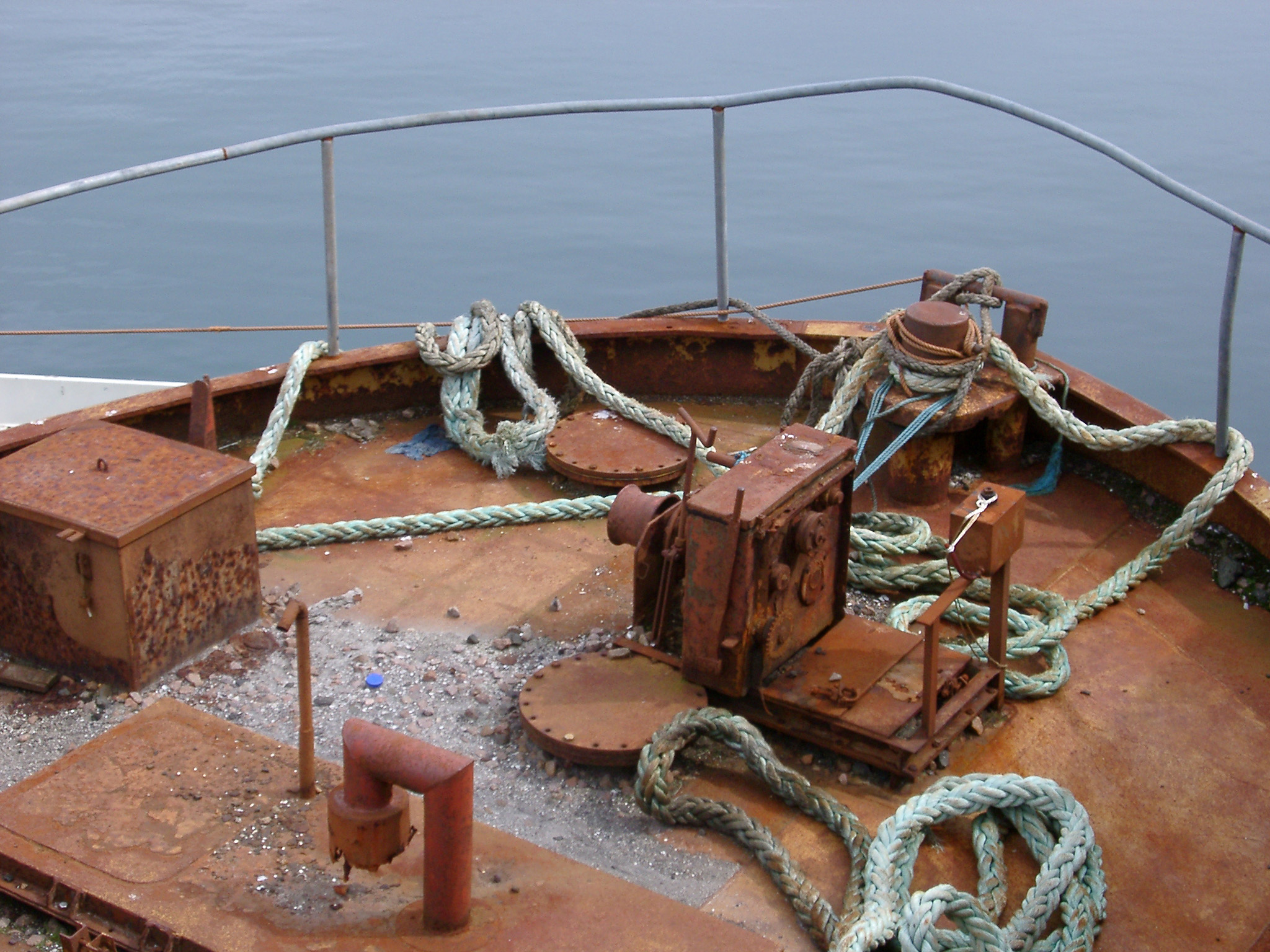Rusty forecastle of a boat with a safety railing around the bow and old ropes and equipment on deck