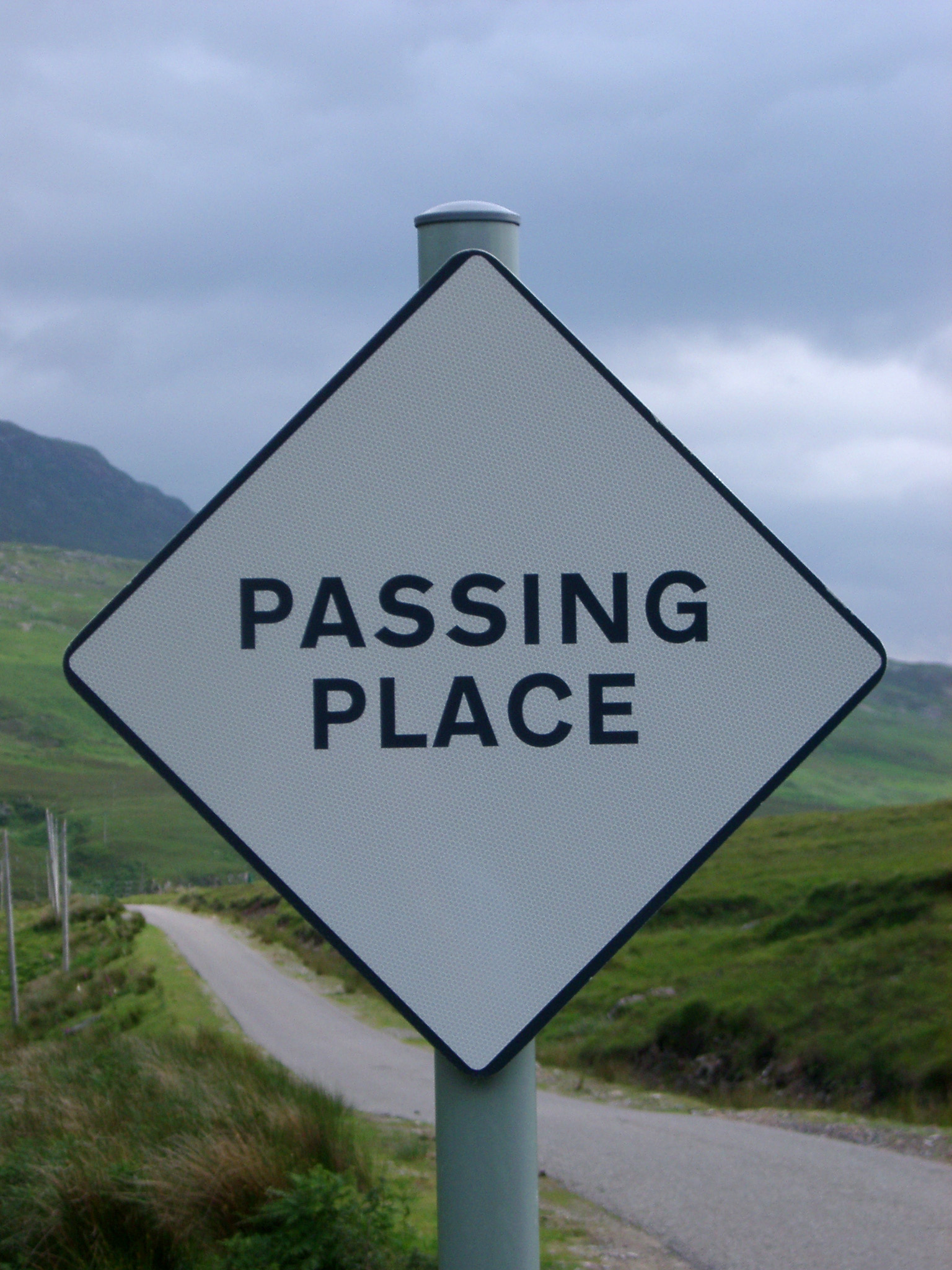 Passing Place roadsign in Scotland on a single lane rural road indicating a safe place for vehicles traveling through the Highlands to pass