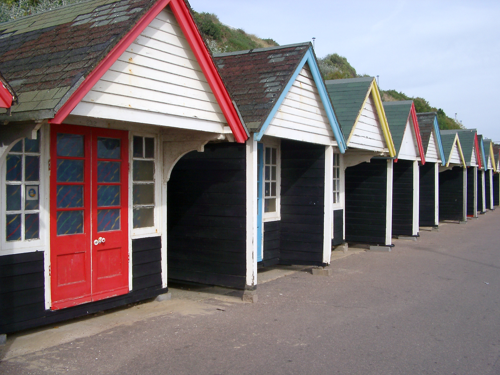 Wooden beach huts with border and doors painted in various colors, aligned along the seashore