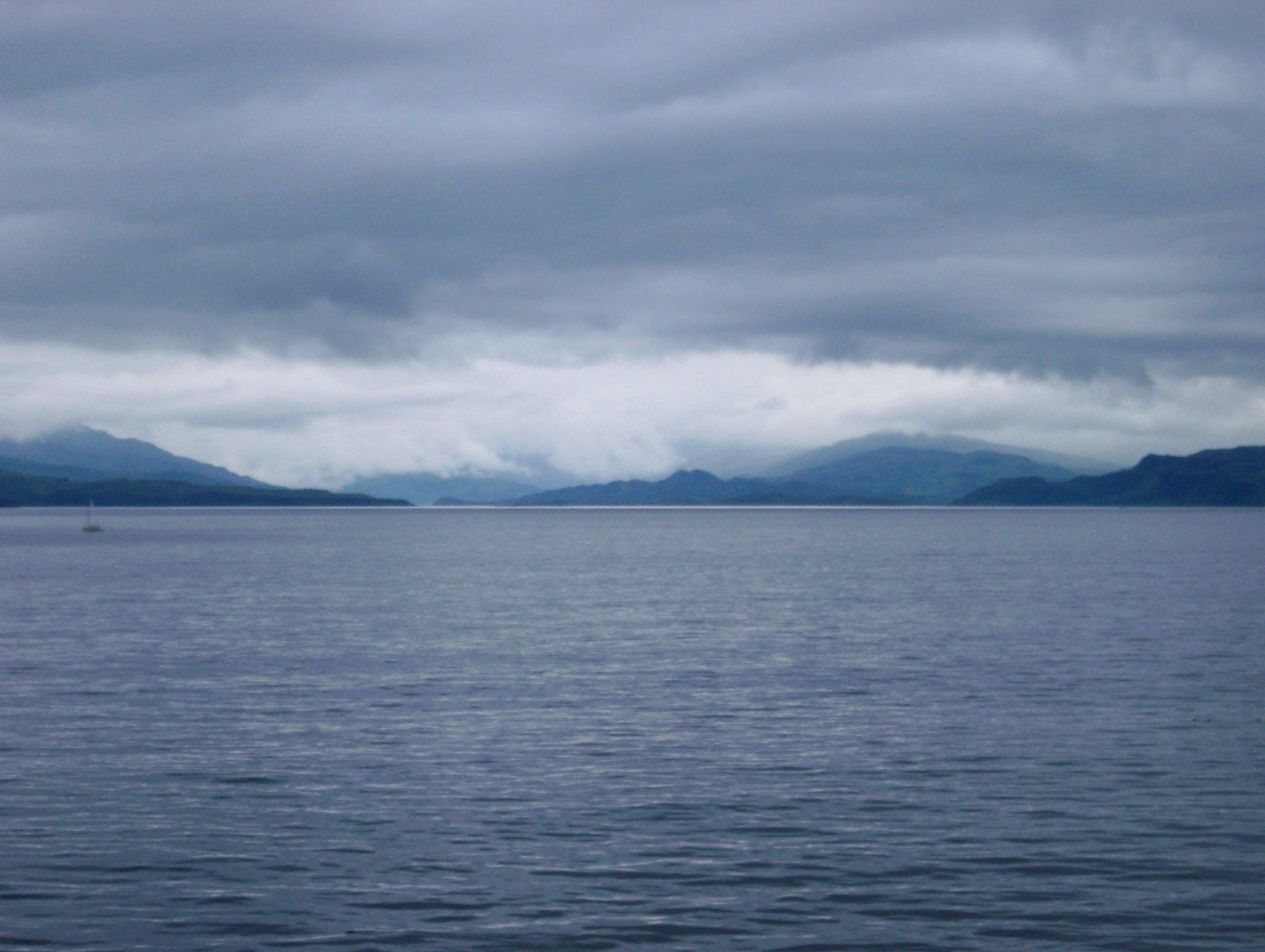 View over a calm ocean on a stormy overcast day of Scottish lochs and distant mountains