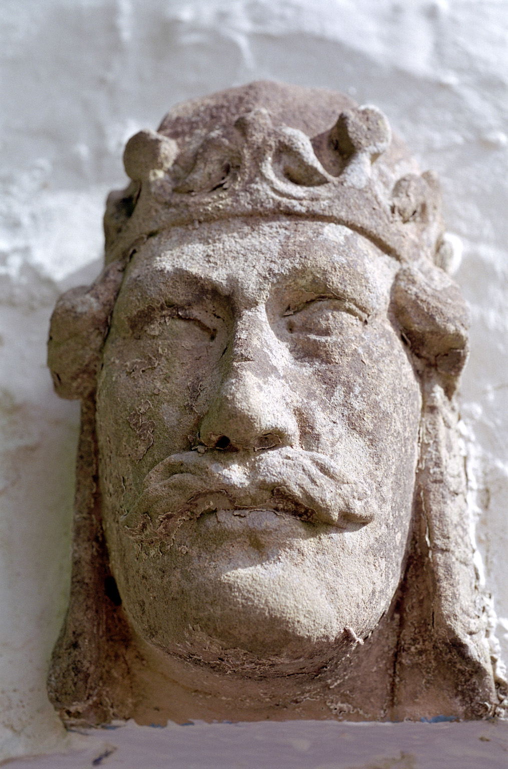 The sculpted stone head of an ancient imposing king wearing a crown, symbol of royal historical authority, close-up
