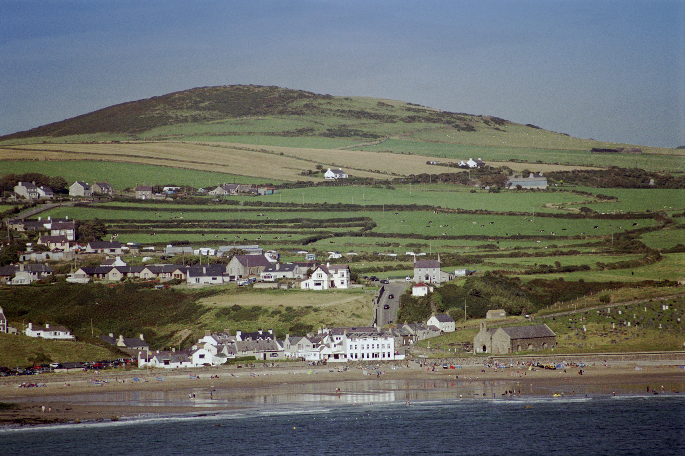 Picturesque view of Aberdaron on the Welsh coast of the Llyn peninsula set amongst lush green rolling hills