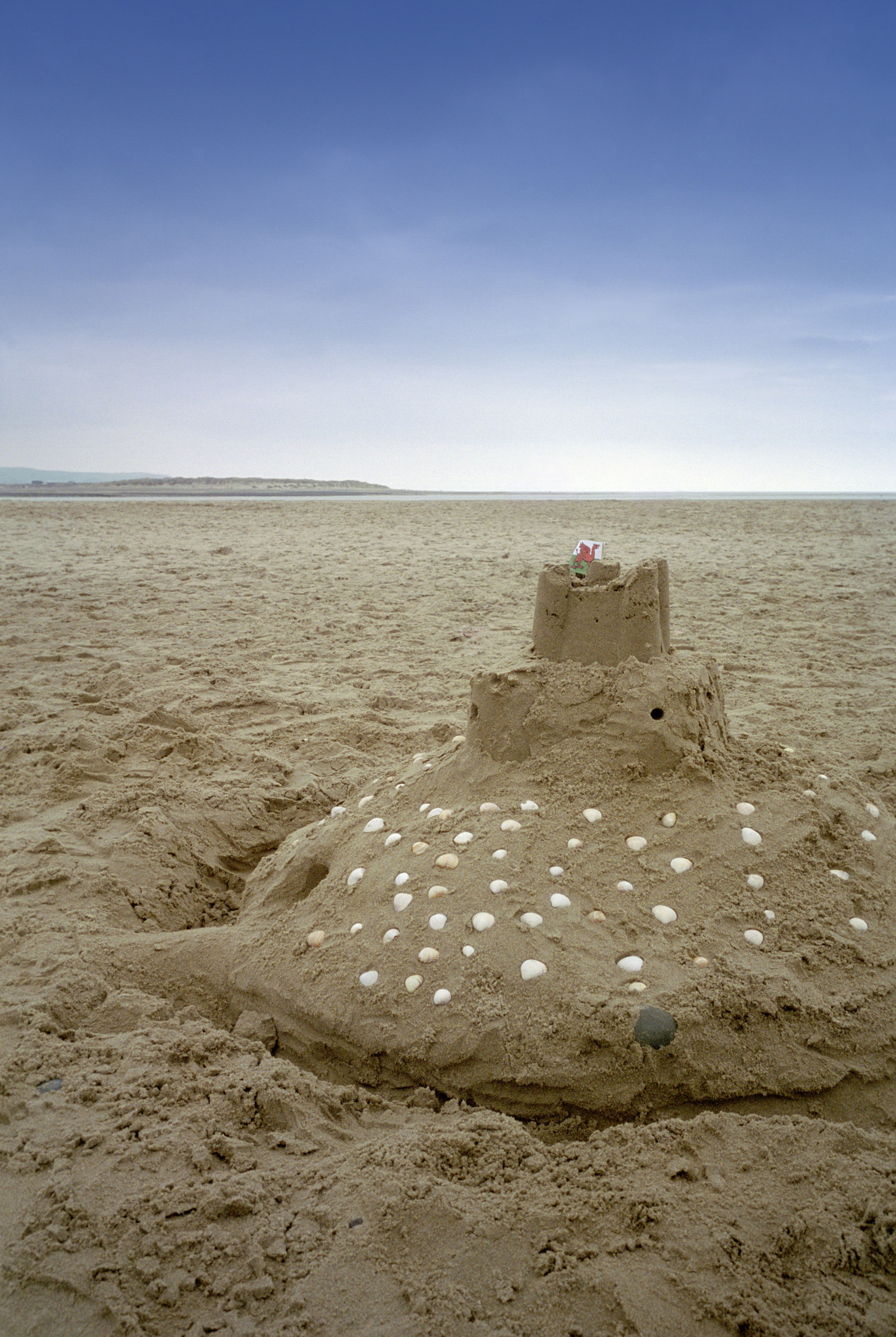 Sandcastle decorated with shells on a beach at the seaside with golden beach sand a reminder of as happy afternoon spent playing in the sand