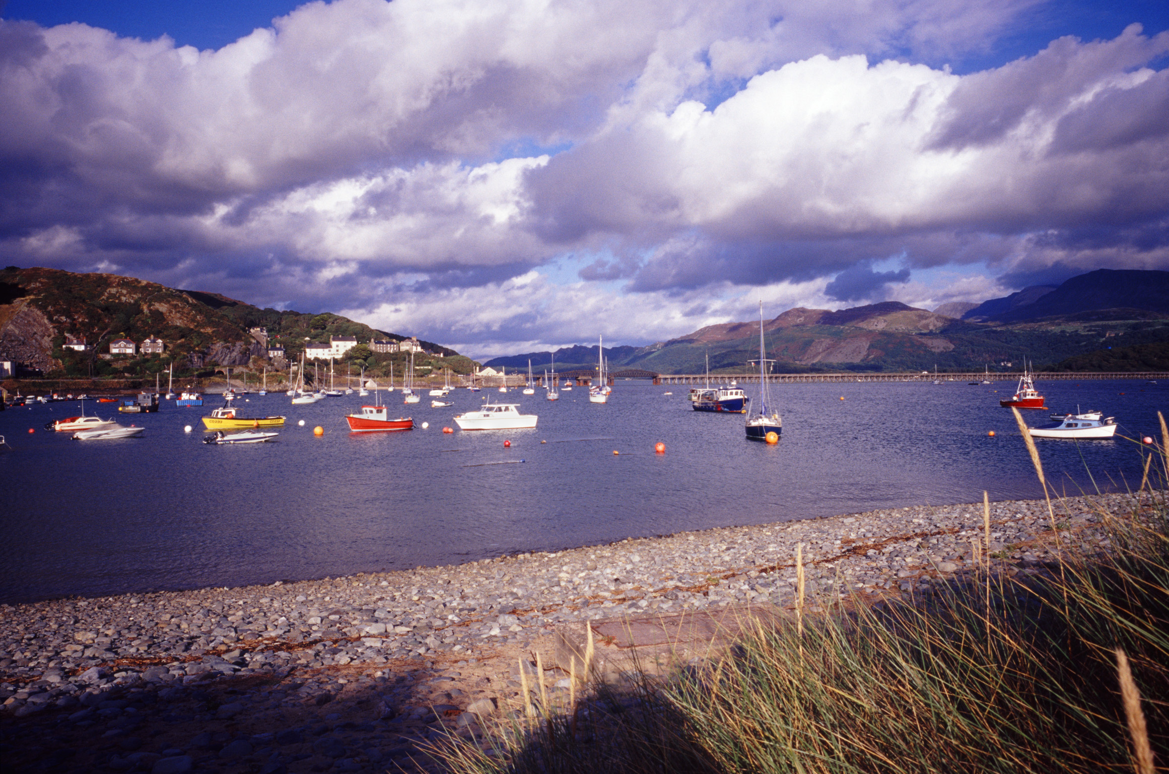 Boats moored in the sheltered water of the harbour at Barmouth, Wales in a picturesque landscape view