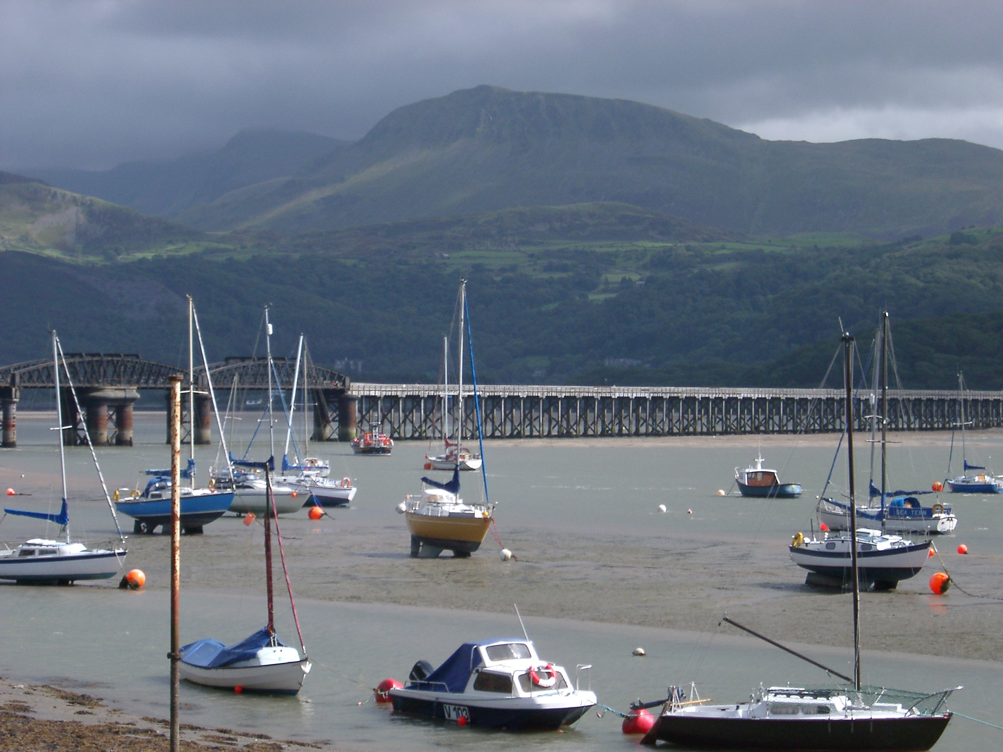 Fishing boats moored in the harbour at Barmouth with the steel railway viaduct crossing the water behind them against a mountain backdrop