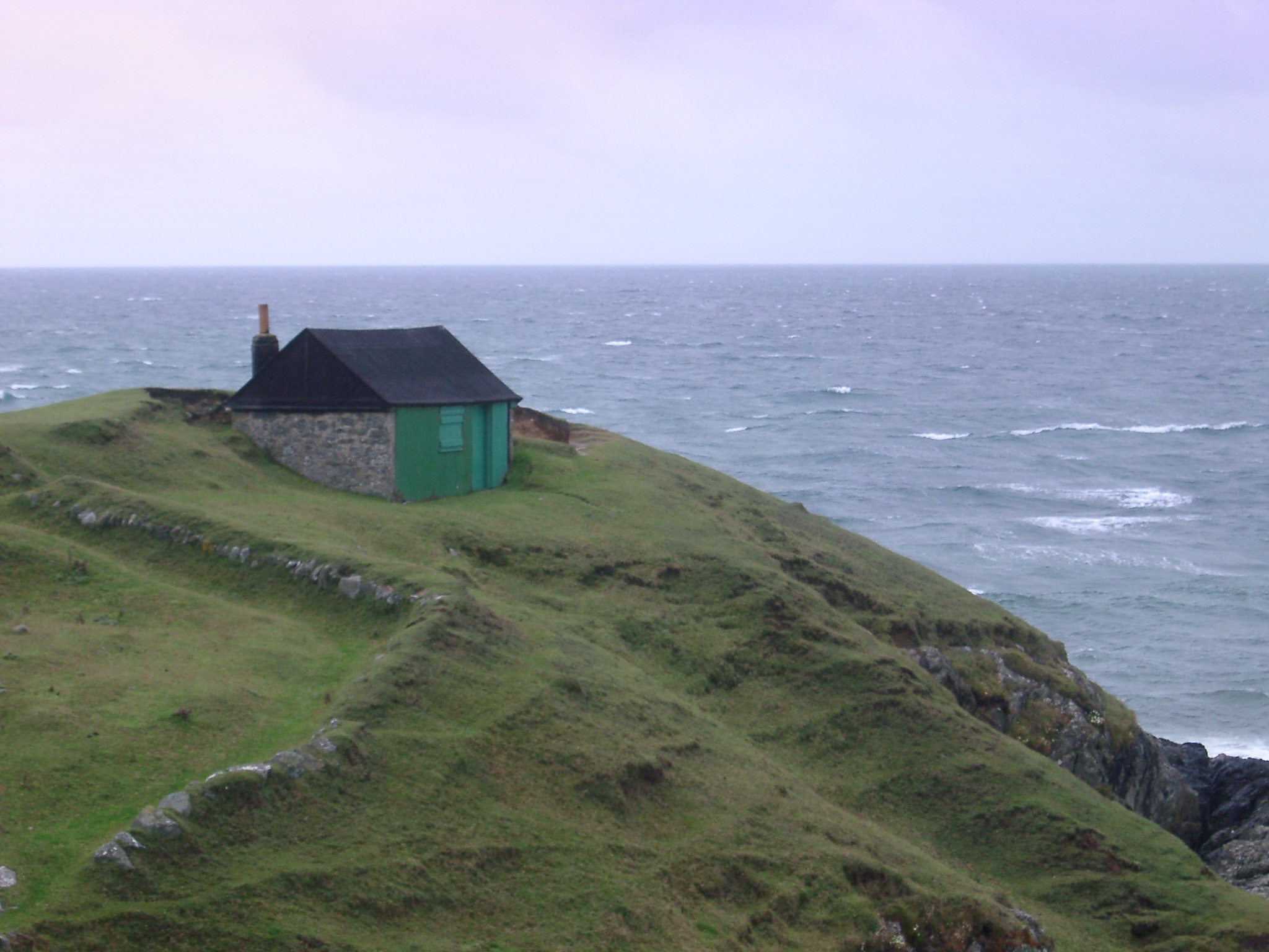 Stormy coastal landscape with the roof of a small hut or cottage on a lush promontory with pastures overlooking a wild ocean with breaking waves