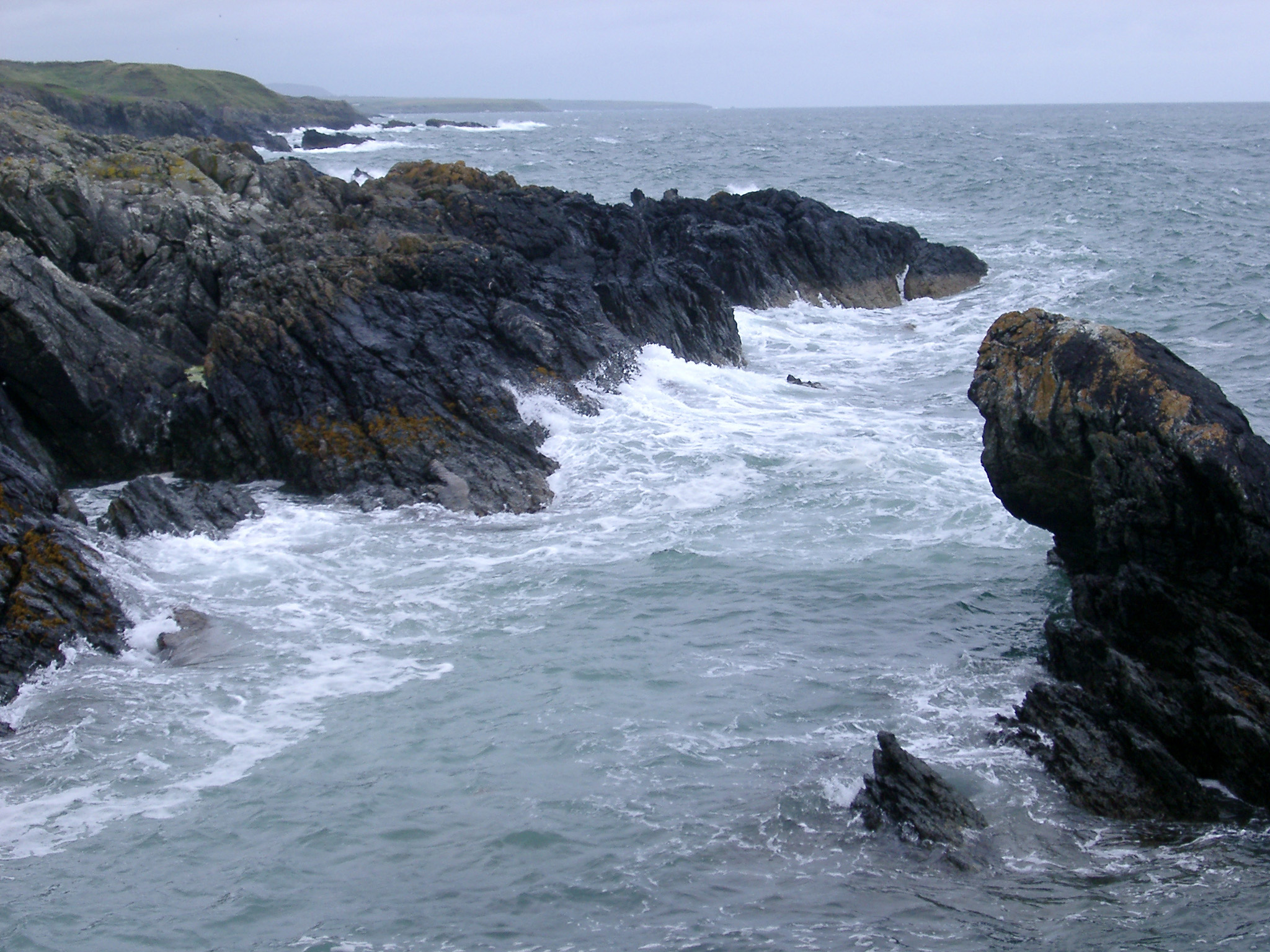 Stormy sea with breaking waves lashing a rocky coastline on a grey misty day