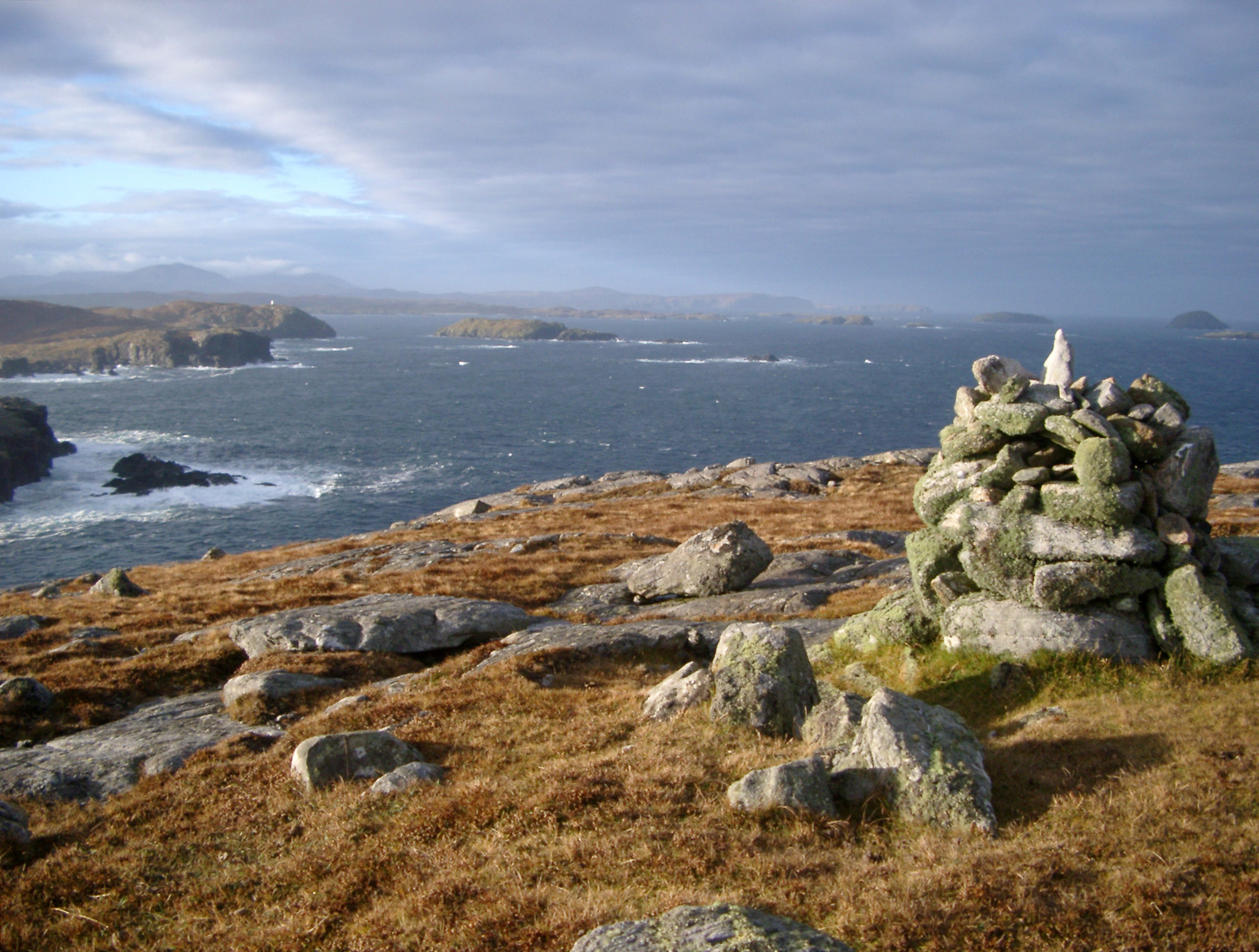 Stone cairn on a coastal headland lookout overlooking the coastline of the Hebrides, Scotland on a stormy day