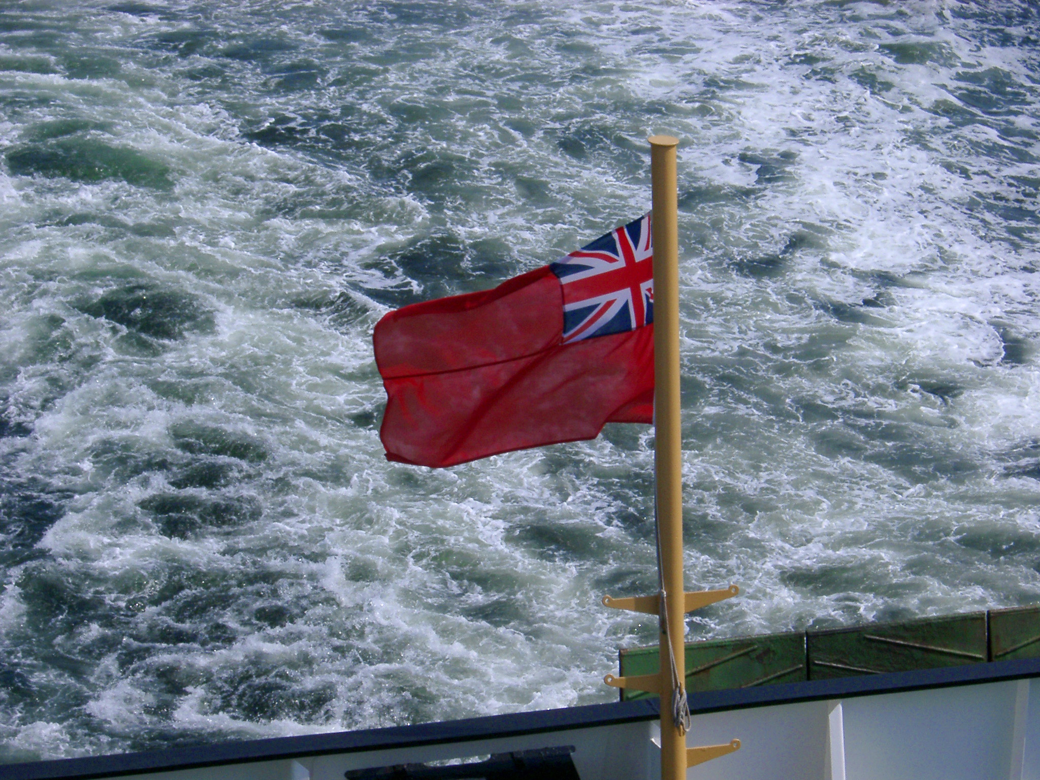 Red Scottish ensign flag flying off the stern of a ferry against the turbulence of the wake mid-ocean during a voyage