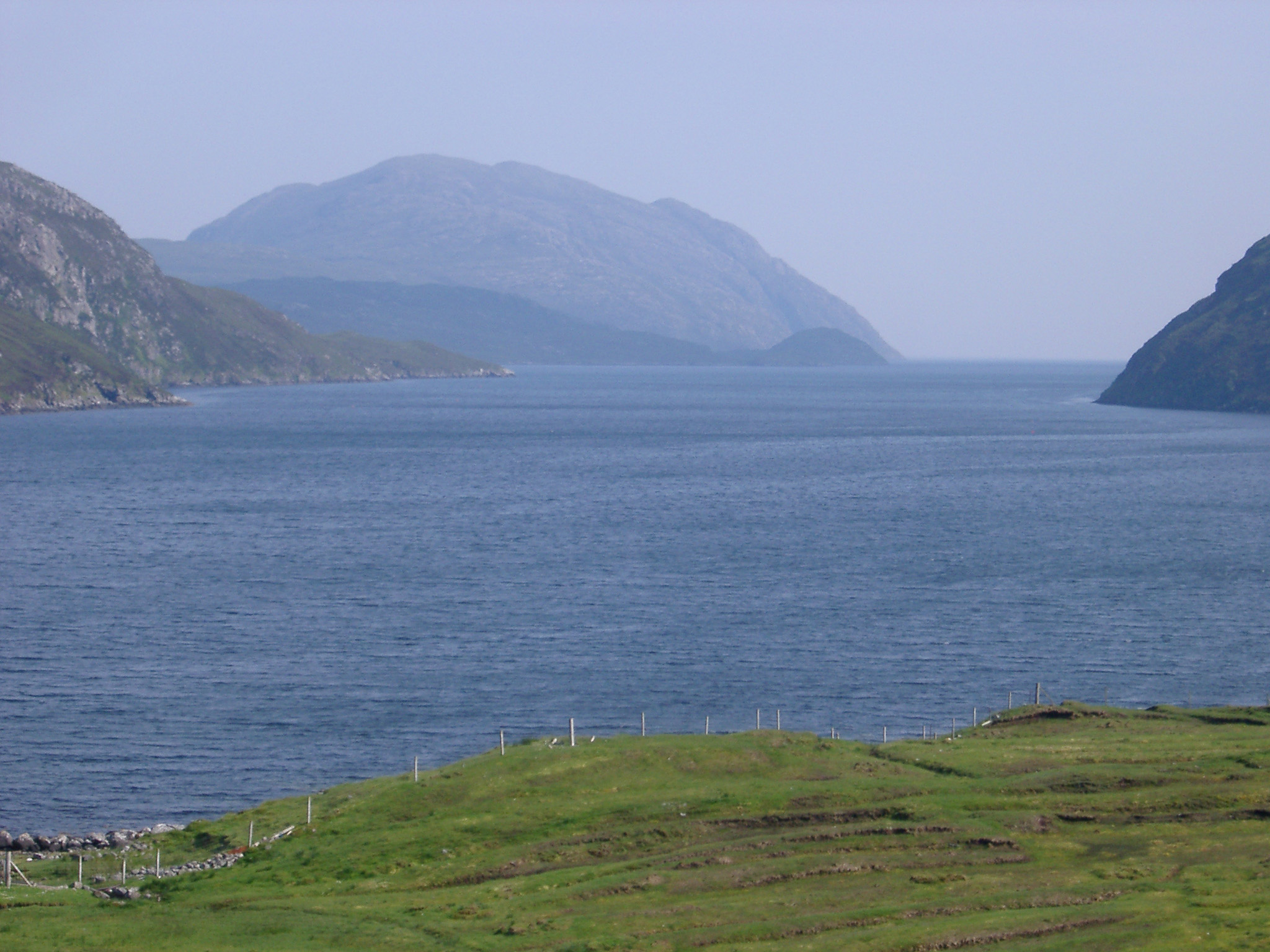 Coastal scene in the Inner Hebrides with a tranquil sheltered loch surrounded by mountain peaks, Scotland