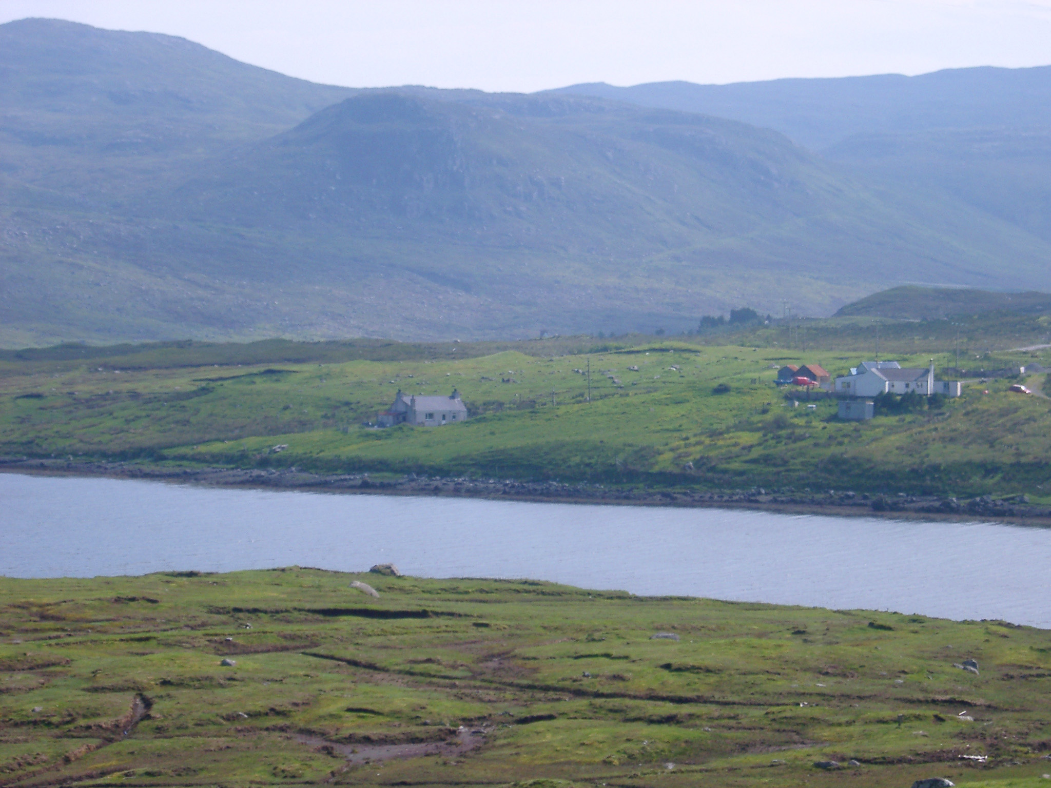 Remote Valley Houses and Green Farmland on Scottish River Shoreline with Hills in Background
