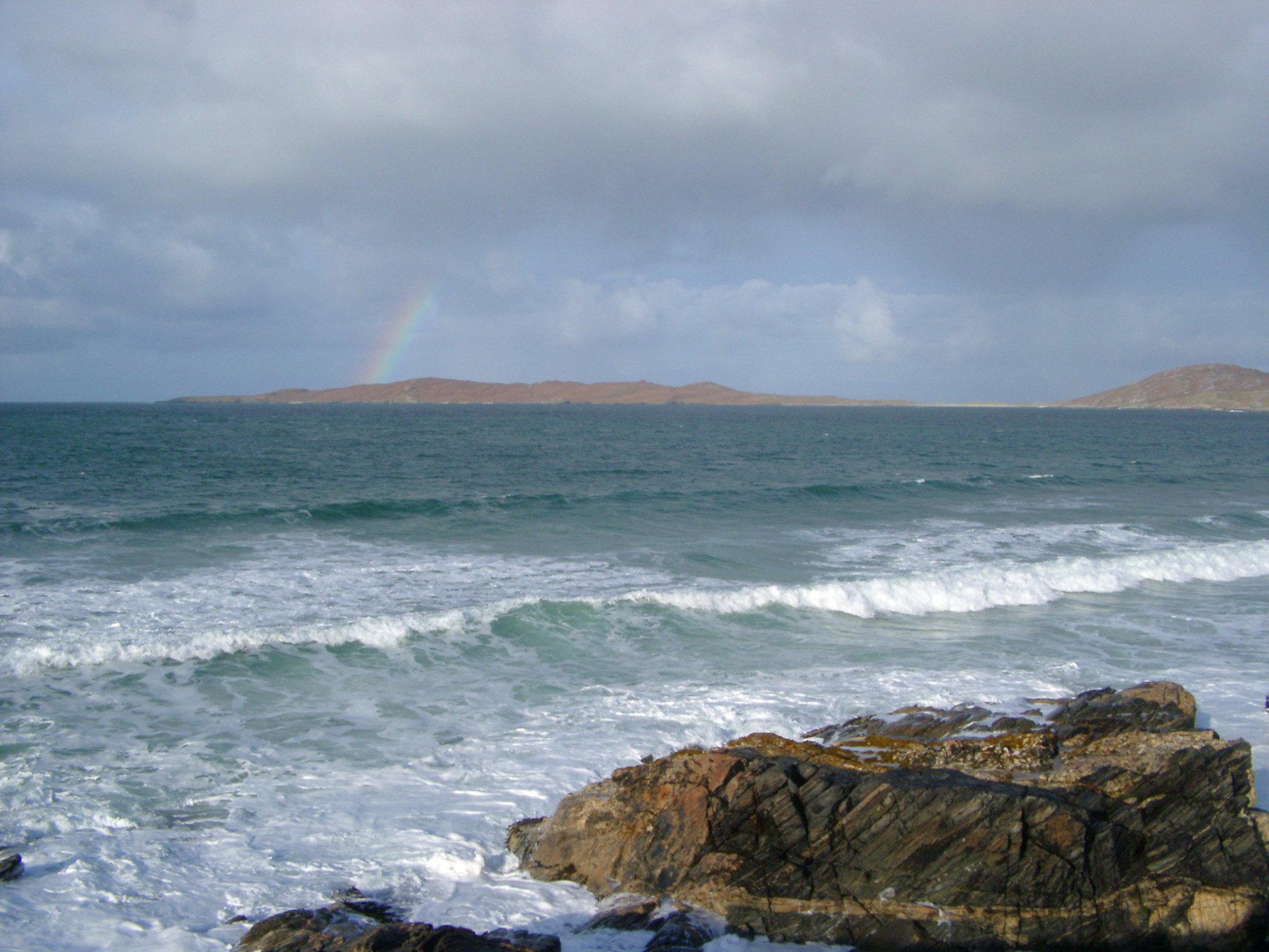 Stormy seascape with breaking white waves and a distant rainbow off the Isle of Harris
