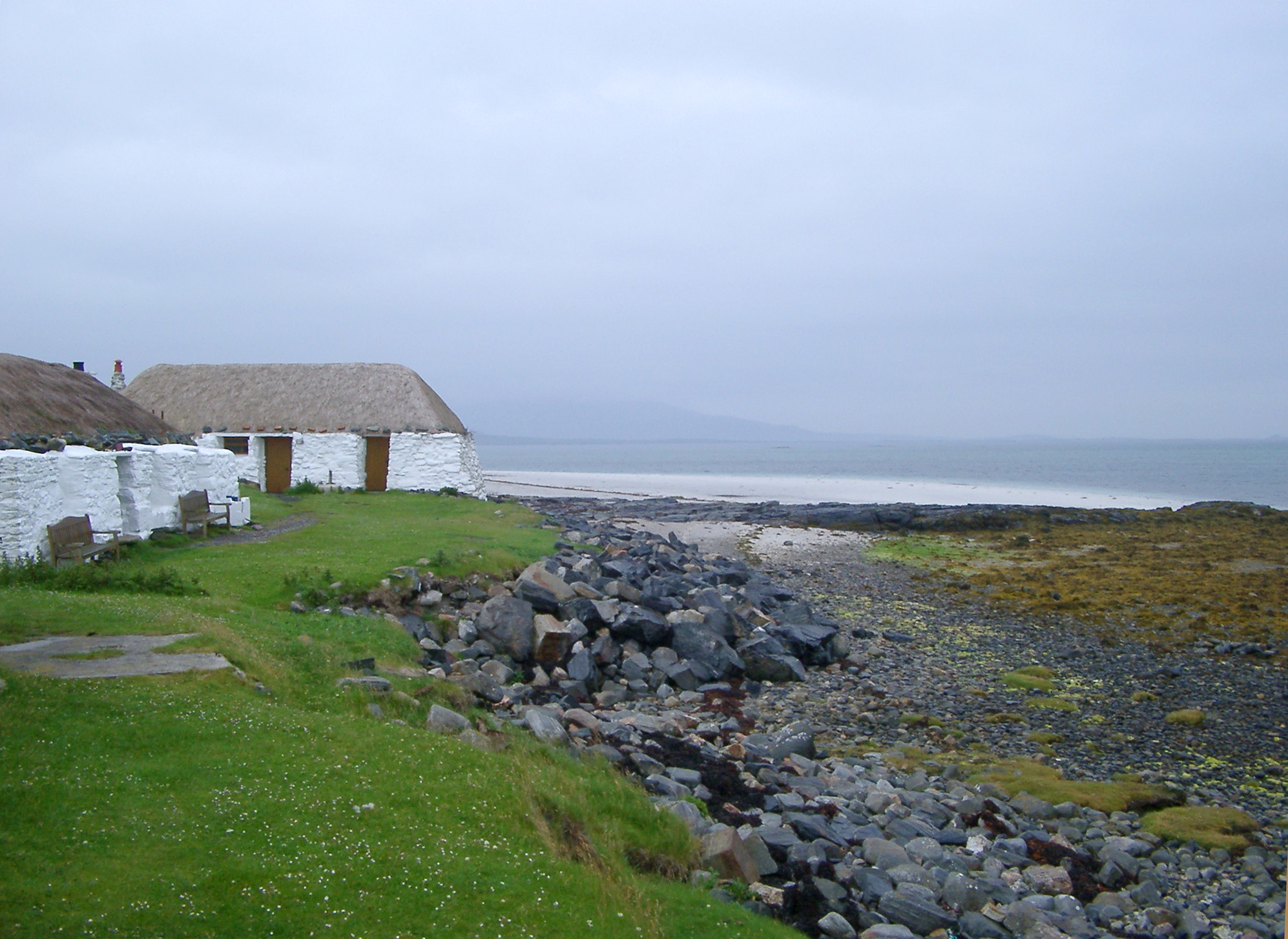 traditional whitewashed thatched youth Hostel on the Isle of Barra in the Outer Hebrides, Scotland overlooking the ocean