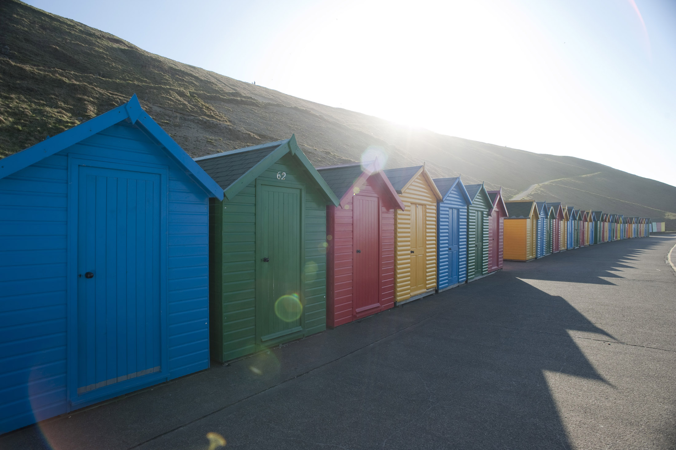 a line of beach huts on the shore at whitbys west cliff