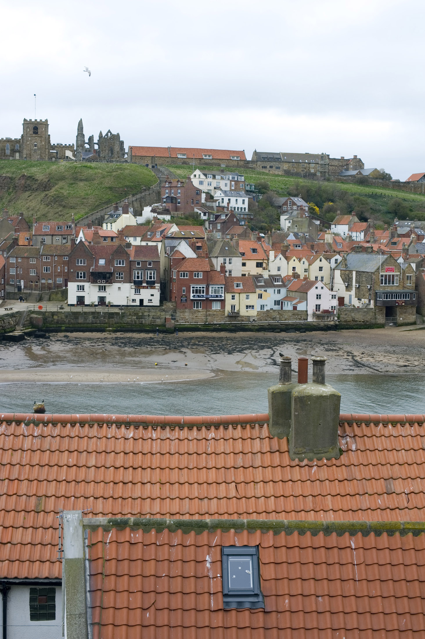 looking over tiled cottage roof tops to the lower harbour and rows of cottages with the abbey and church on the hill