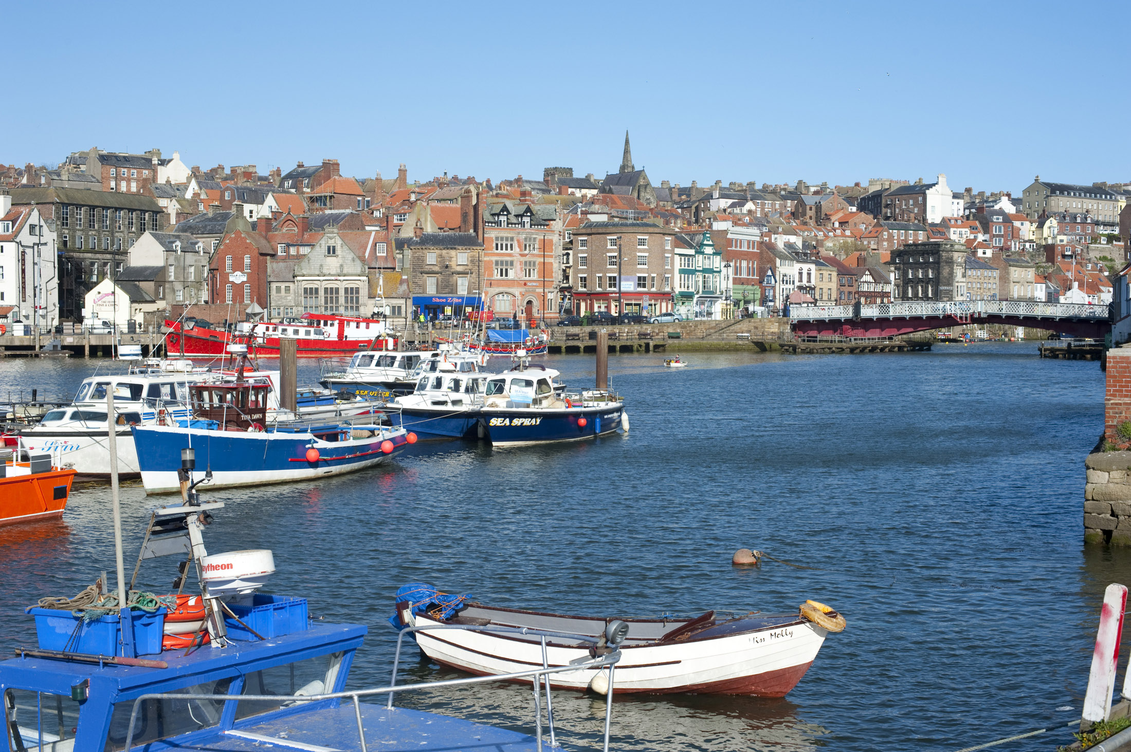 boats moored in the upper harbour of whitby, the swing bridge can be seen at the right leading to the lower harbour
