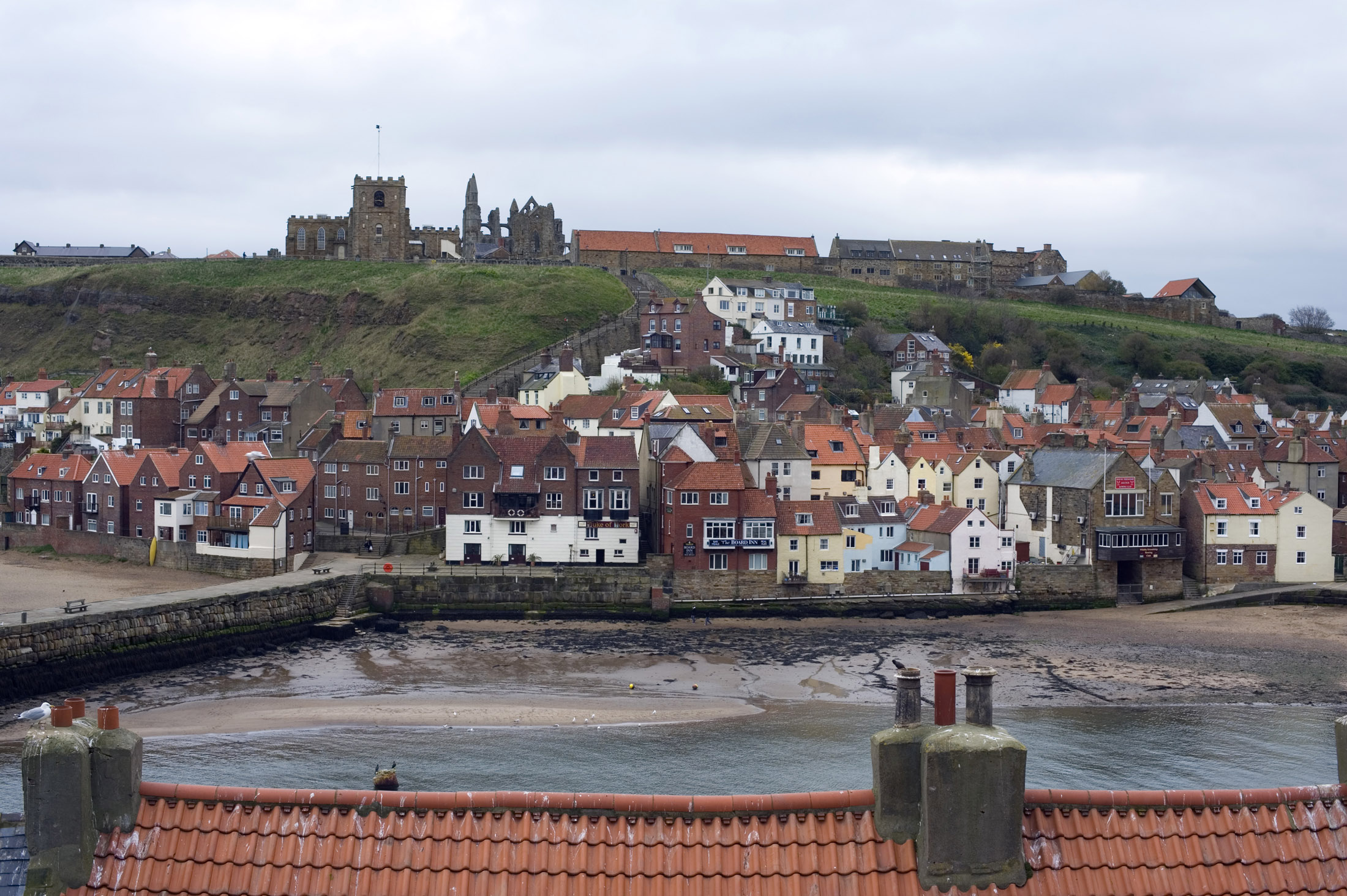 a view of whitby from west cliff looking across the lower harbour to rows of cottages with the abbey and church on the hill