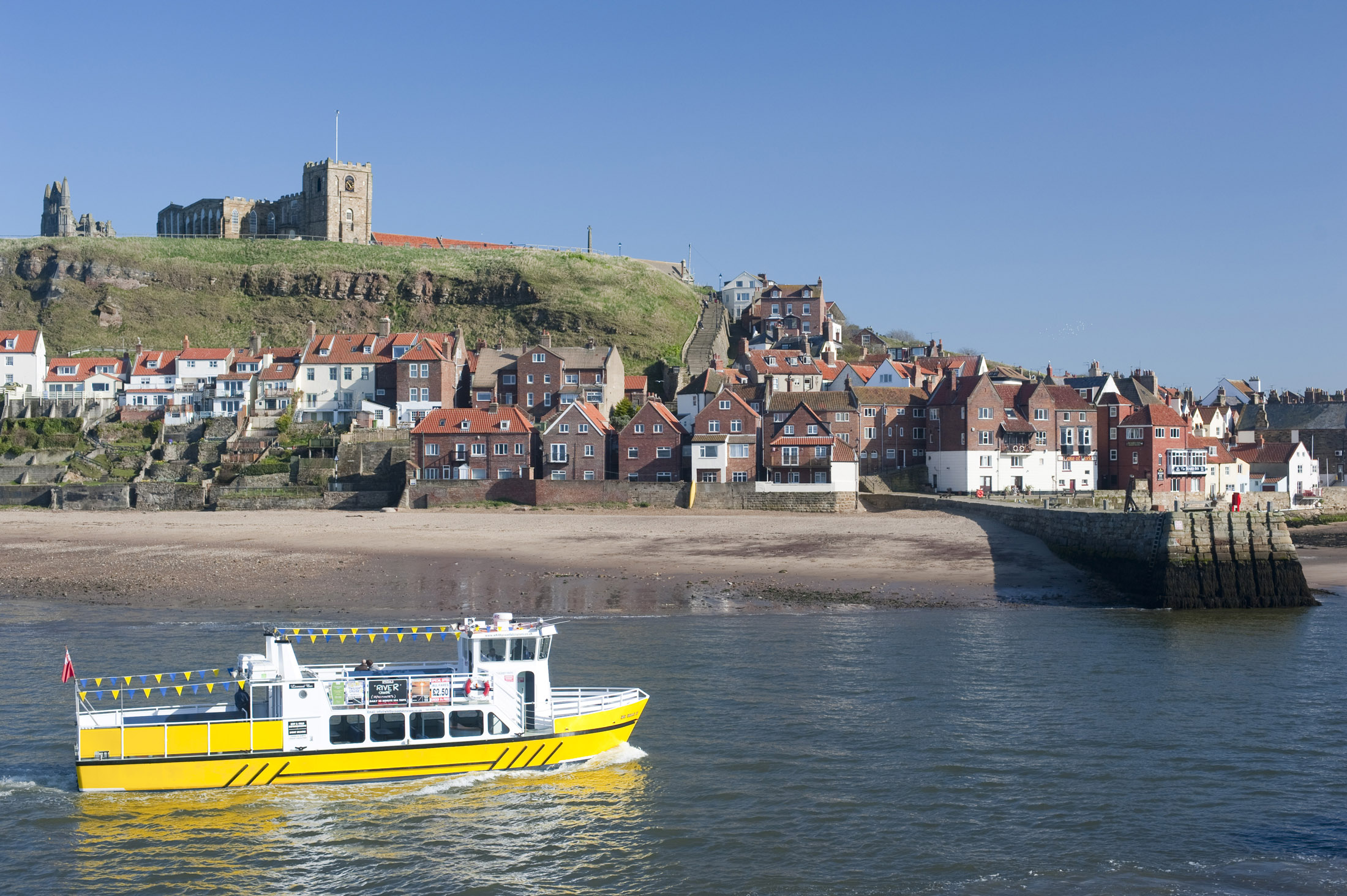 bright yellow trourist cruise boat on whitby lower harbour with the abbey behind