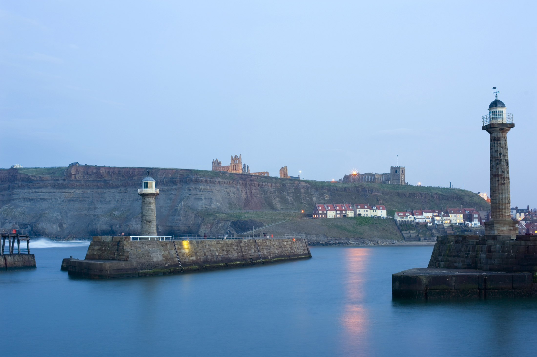 a still dusk over whitby lower harbour, with the piers, lighhouses, fishermans cottages and the abbey on the hill in view