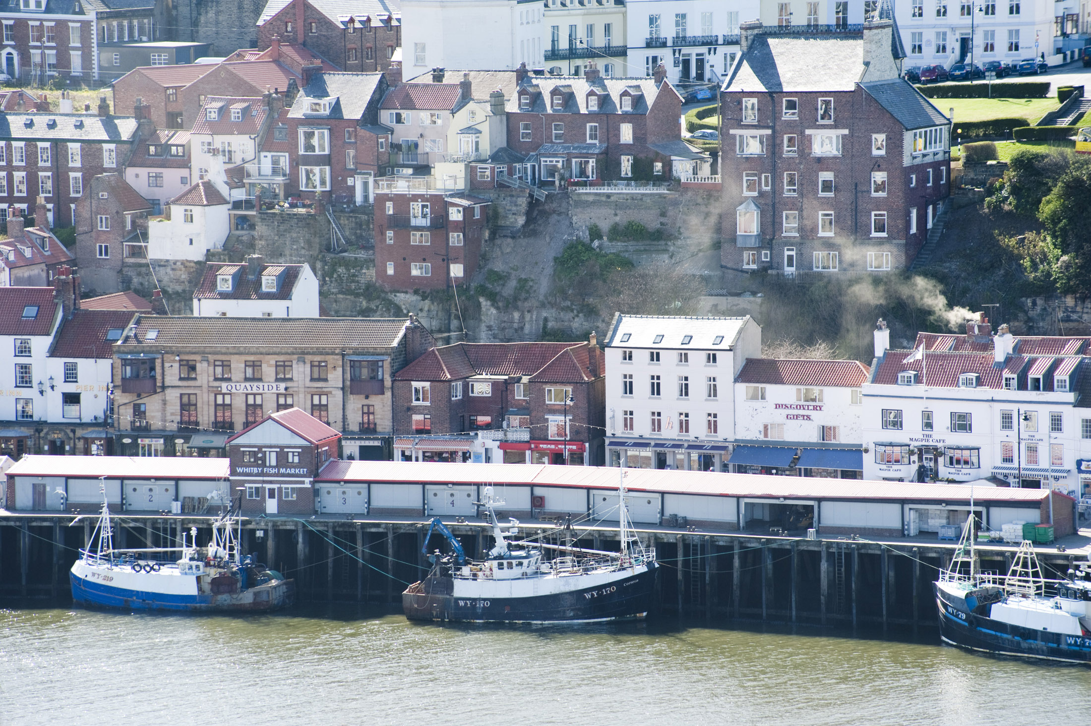 fishing boats docked along the quayside fish market at whitby