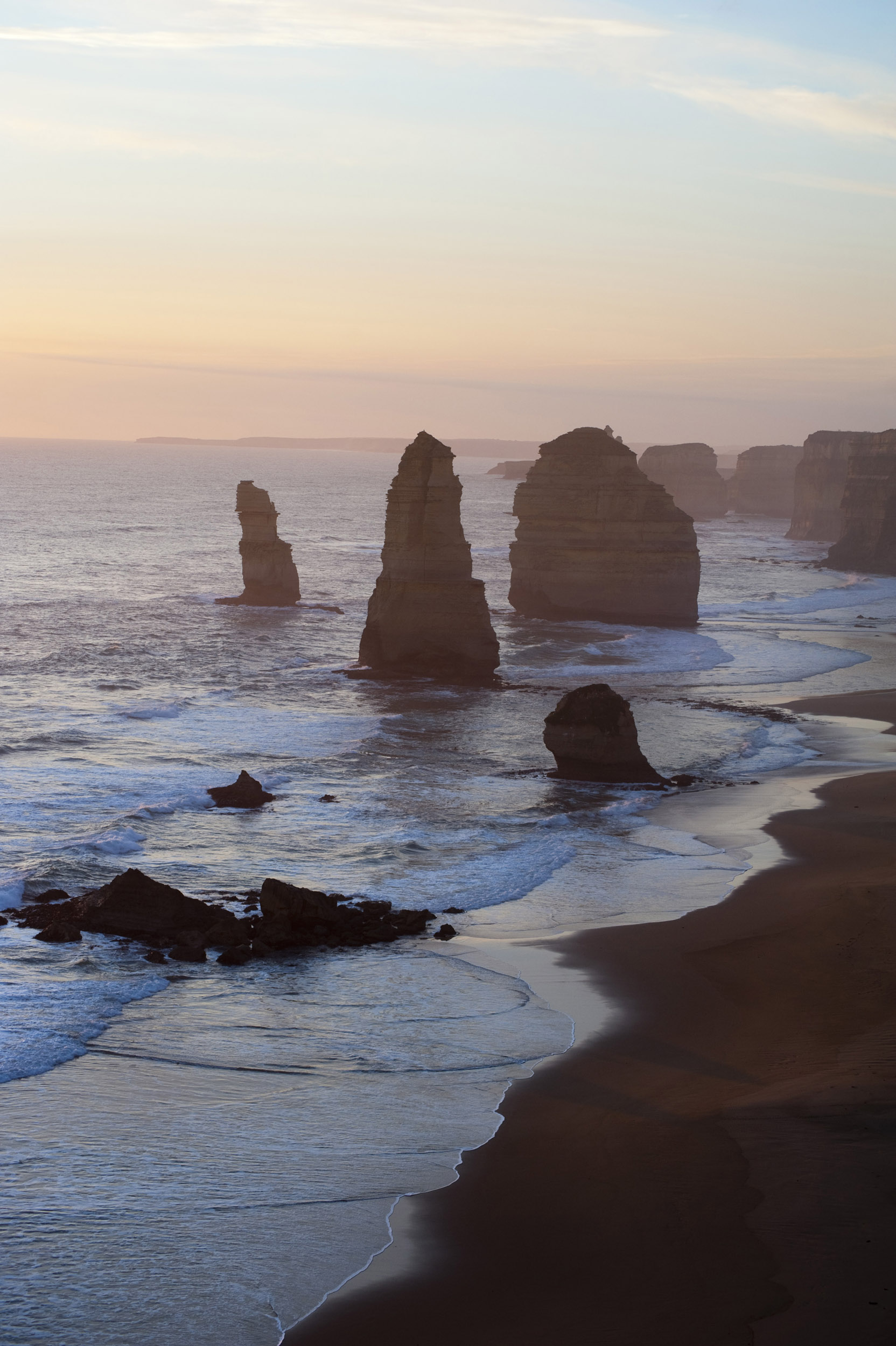 A beautiful sunset and the silhouetted coastline surrounding the 12 Apostles on the Great Ocean Road in Victoria, Australia.
