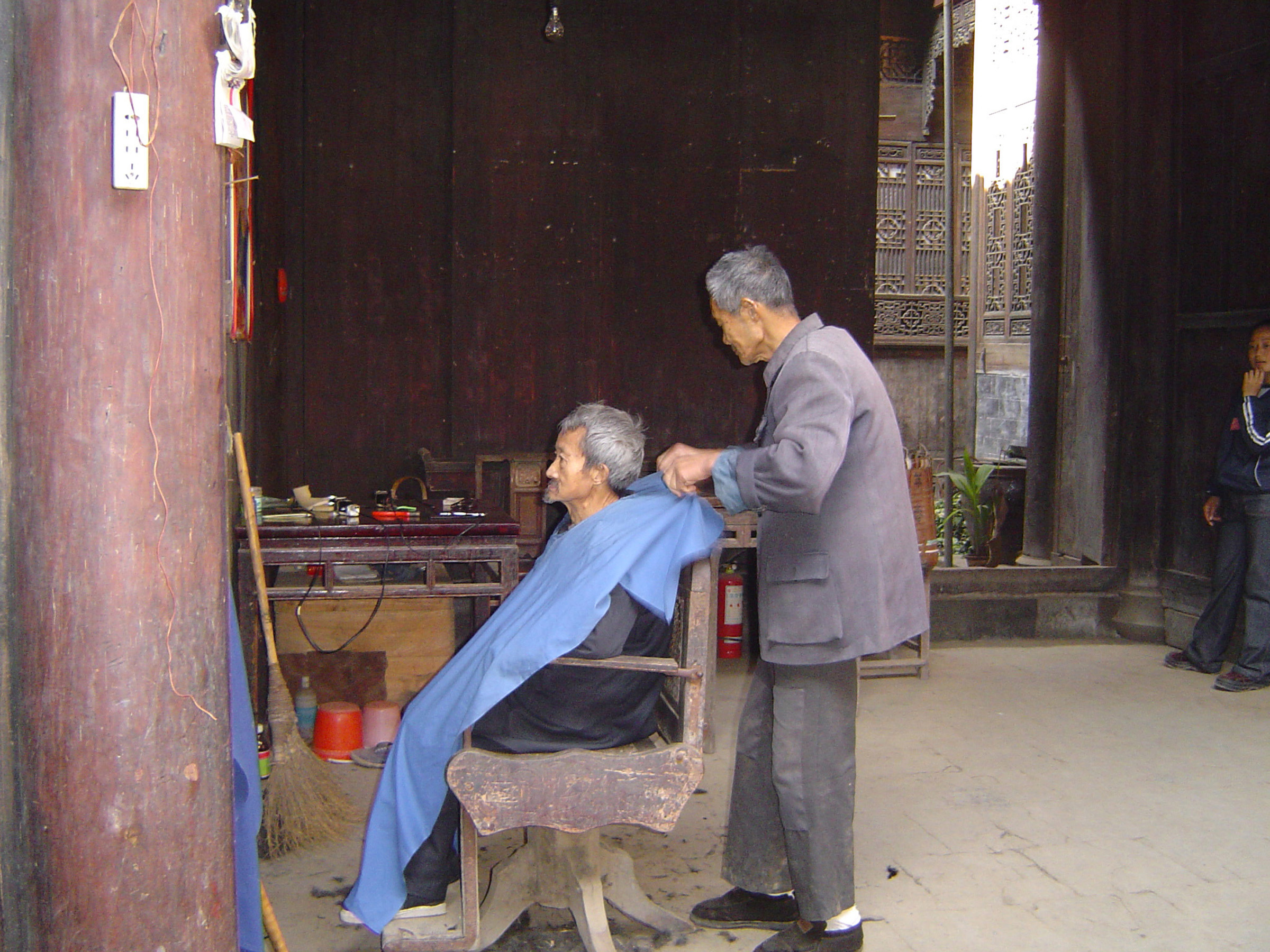 Old Professional Chinese Barber with Old Male Customer at Vintage Barber Shop in China.
