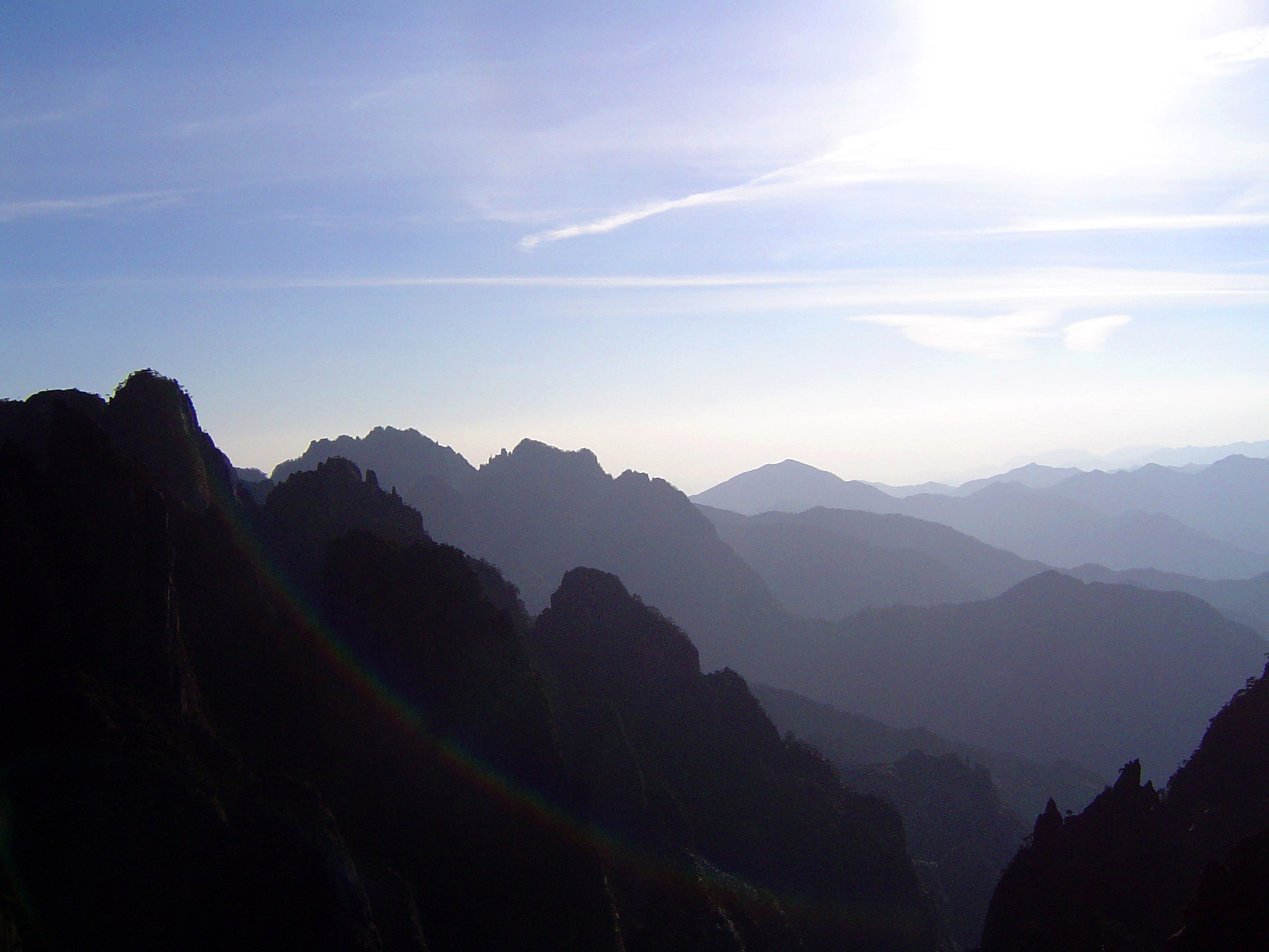 Yellow Mountain, China, vista with the Huangshan mountain range stretching away into the distance on a hazy sunny day