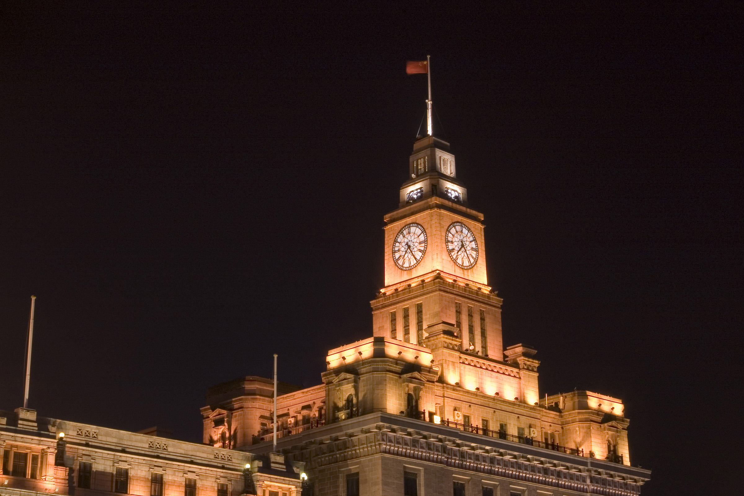 Customs House, or the Bund, Shangai, China illuminated at night with a flag flying at full mast above